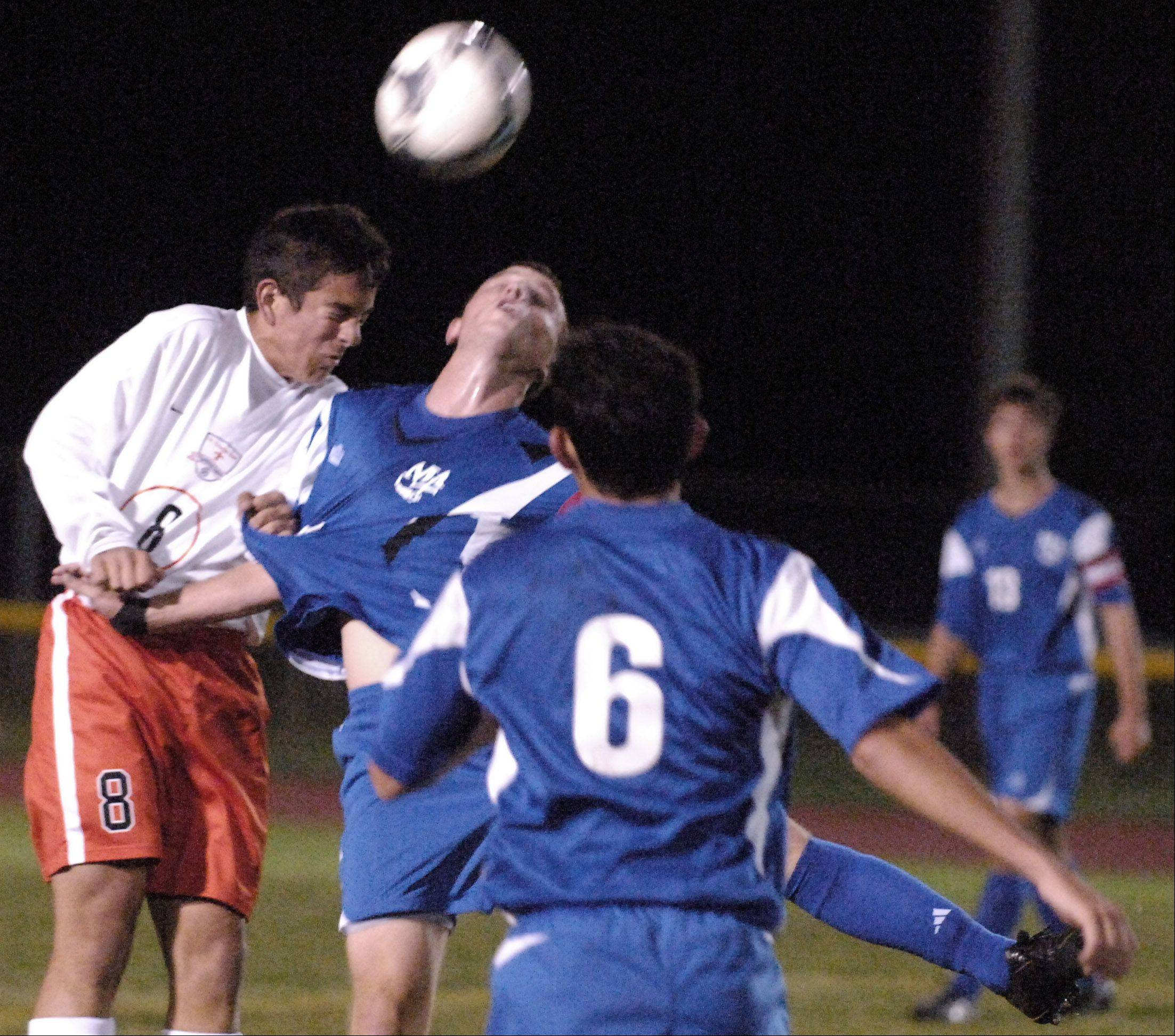 St. Charles East's Michael Macek battles Marmion's Mick Maley for a header during Thursday's action at the St. Charles East High School varsity soccer tournament.