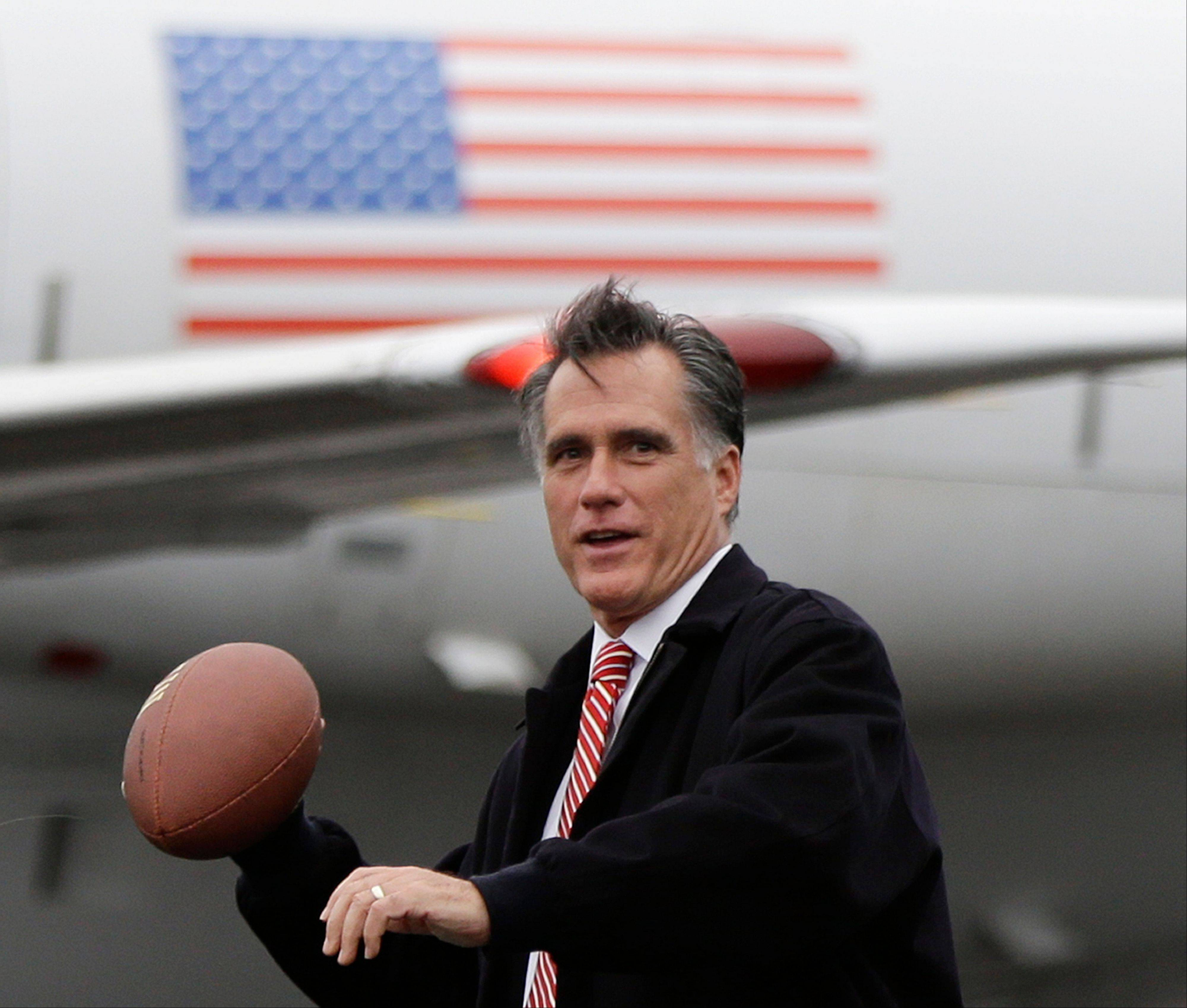 Republican presidential candidate and former Massachusetts Gov. Mitt Romney holds a football Friday on the tarmac of Akron-Canton Regional Airport in Akron, Ohio.