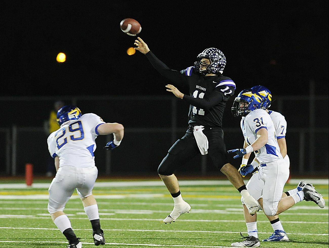 Rolling Meadows� Jack Milas lofts a pass from mid-air to Alex Niecikowski for a 64-yard completion in Class 6A first-round playoff action Friday at Meadows.