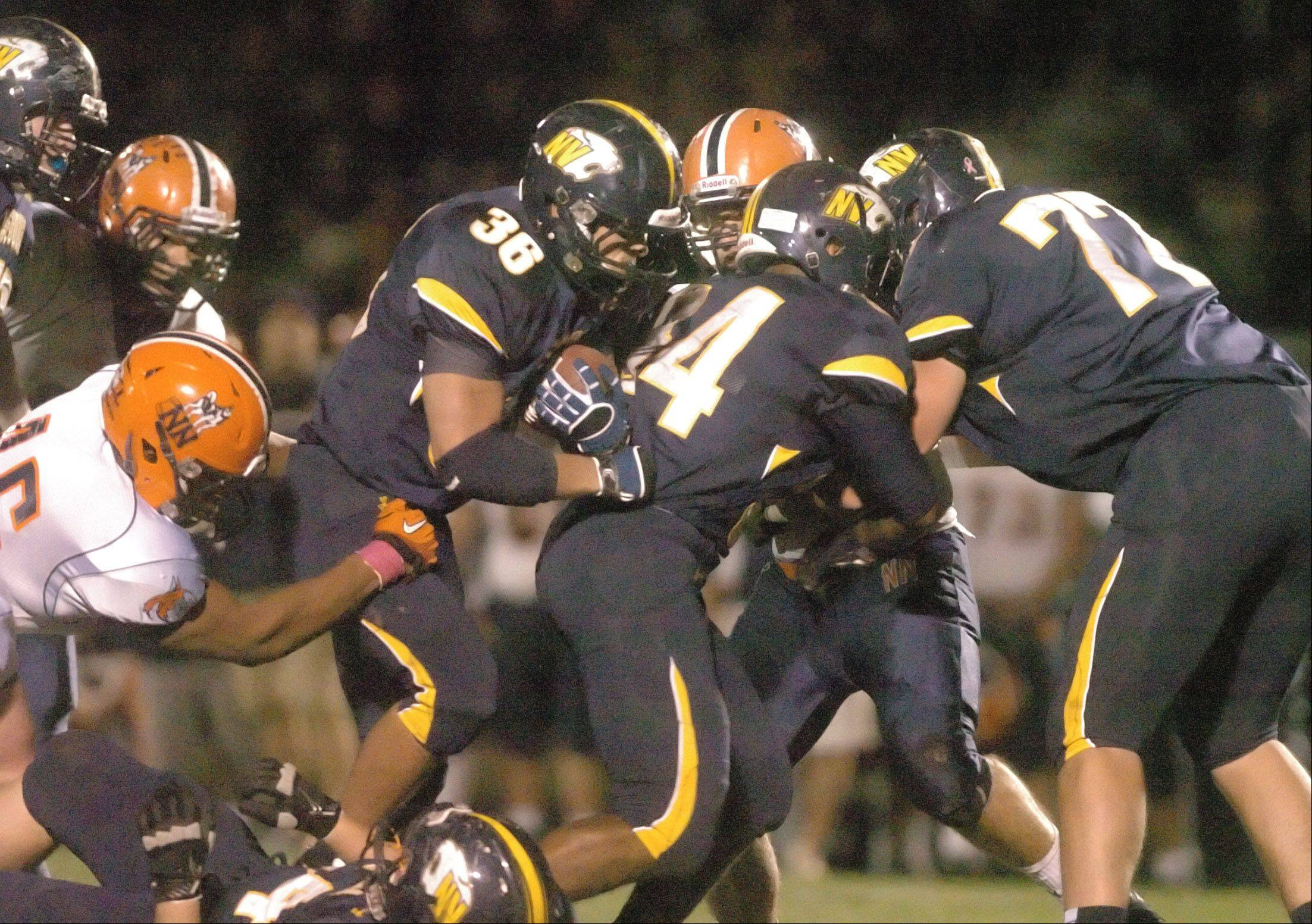 Joey Rhattigan of Neuqua ,center, moves the ball during the Naperville North at Neuqua Valley football game Friday.
