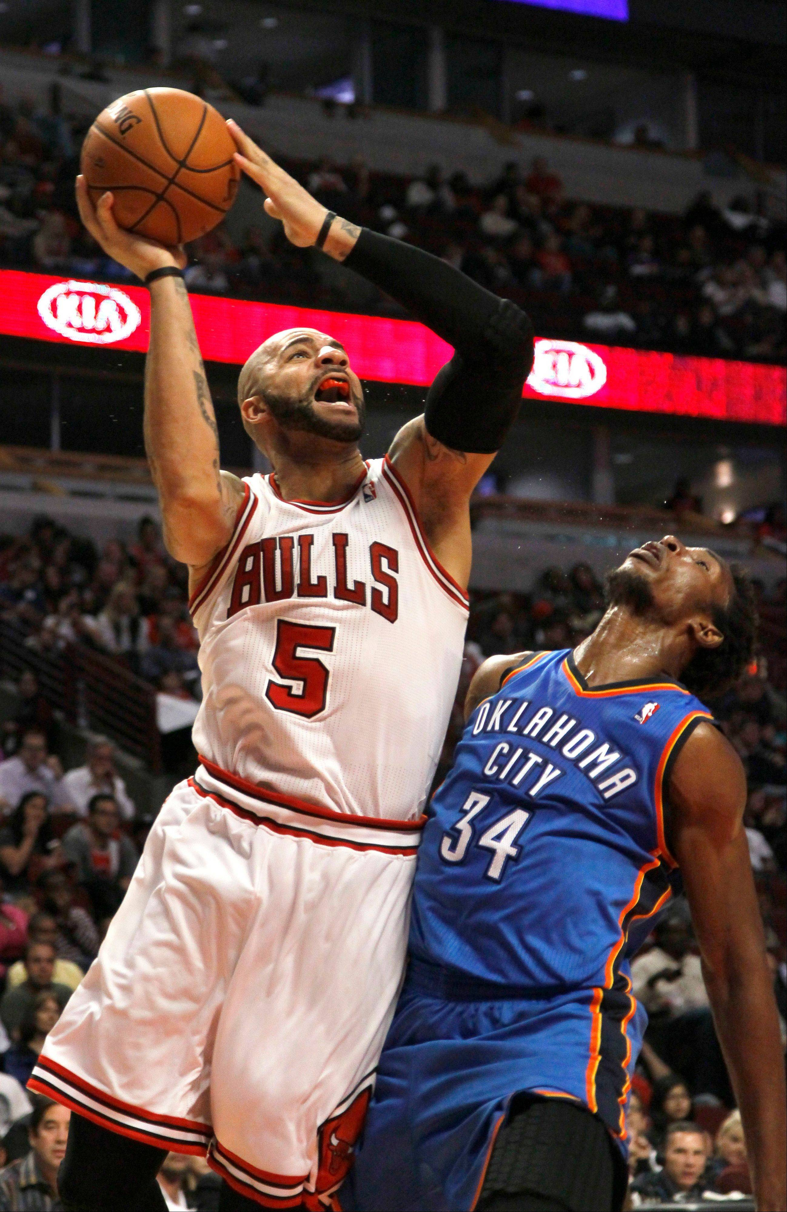 Chicago Bulls forward Carlos Boozer (5) shoots over Oklahoma City Thunder center Hasheem Thabeet during the second half of an NBA preseason basketball game, Tuesday, Oct. 23, 2012, in Chicago. The Bulls won 94-89. Boozer had 24 points, 12 rebounds and five assists. (AP Photo/Charles Rex Arbogast)