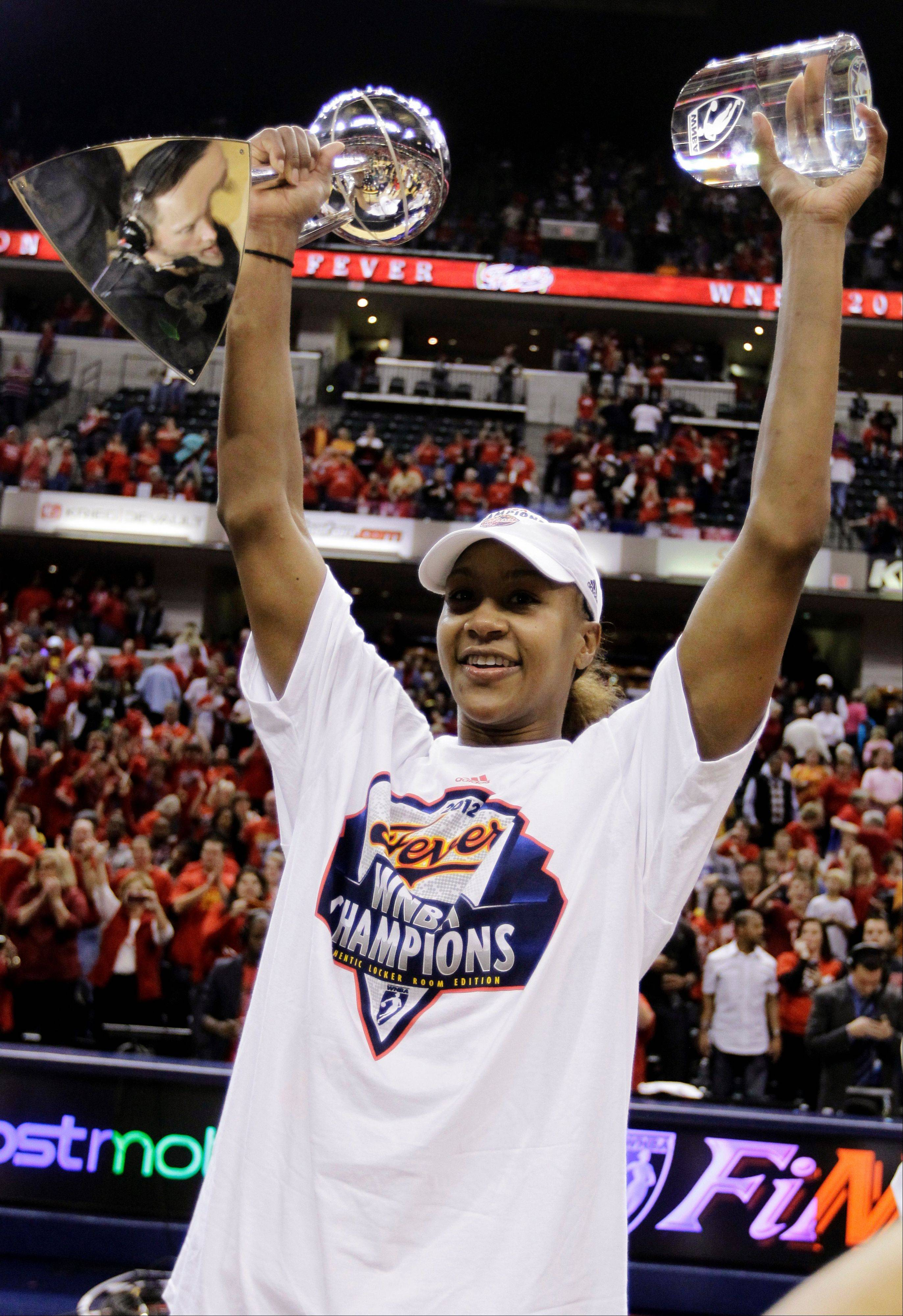 Indiana Fever star Tamika Catchings celebrates with the WNBA championship trophy and Finals MVP award.
