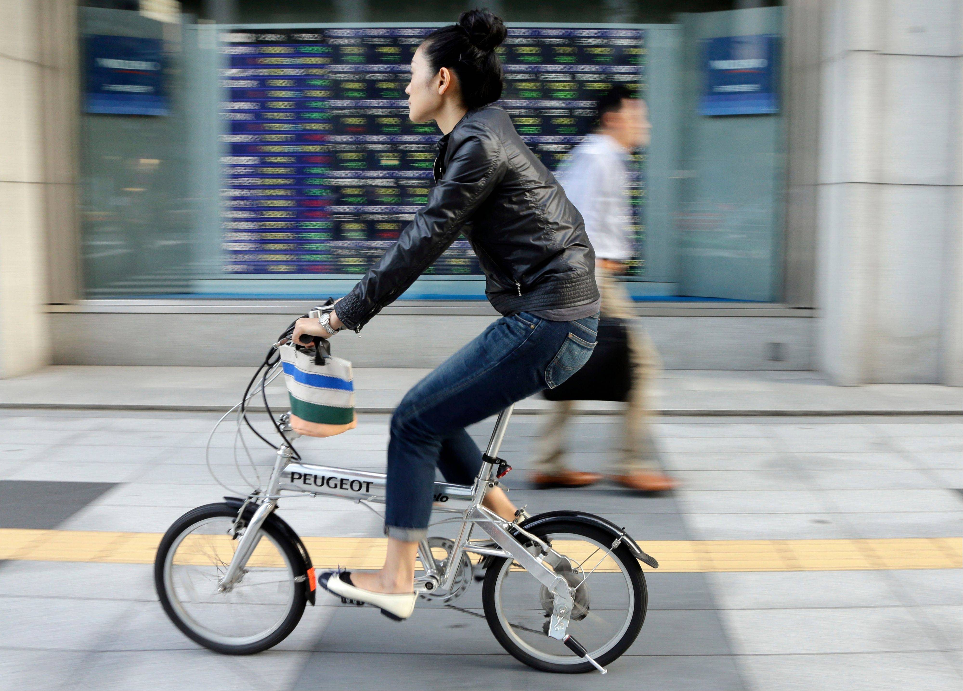 A woman pedals pasts an electronic stock board outside a securities firm in Tokyo, Friday