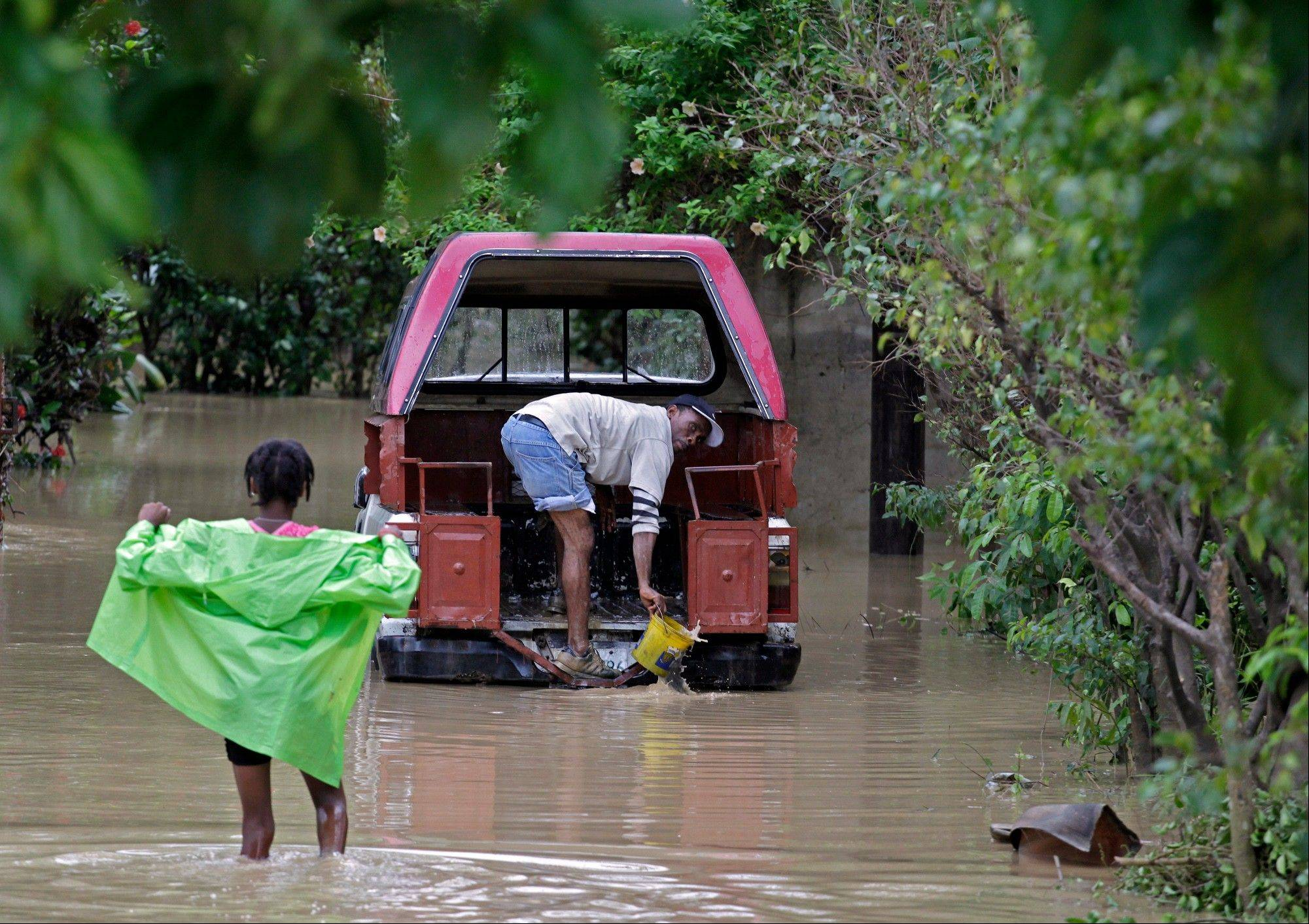 A Haitian man removes mud and flood water from his truck, caused by heavy rains from Hurricane Sandy.