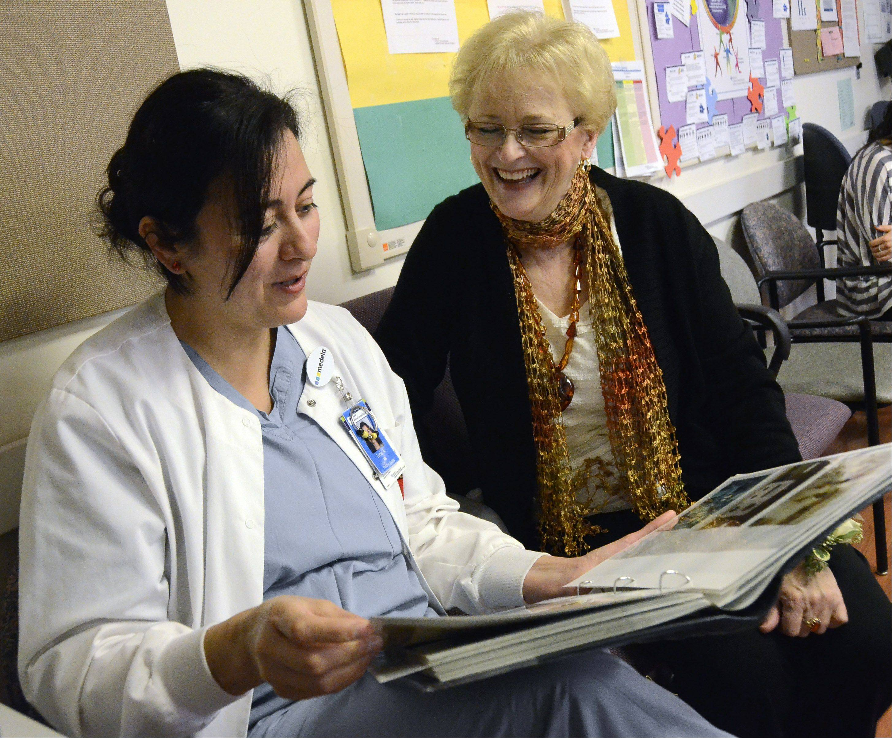 Advocate Lutheran General Hospital nurses Lucia Arenas, left, and Ann Skwarek of Prospect Heights, look at photos of Skwarek's 40 years of service at Advocate Lutheran General Hospital. Skwarek started working in the neonatal intensive care unit shortly after it opened.
