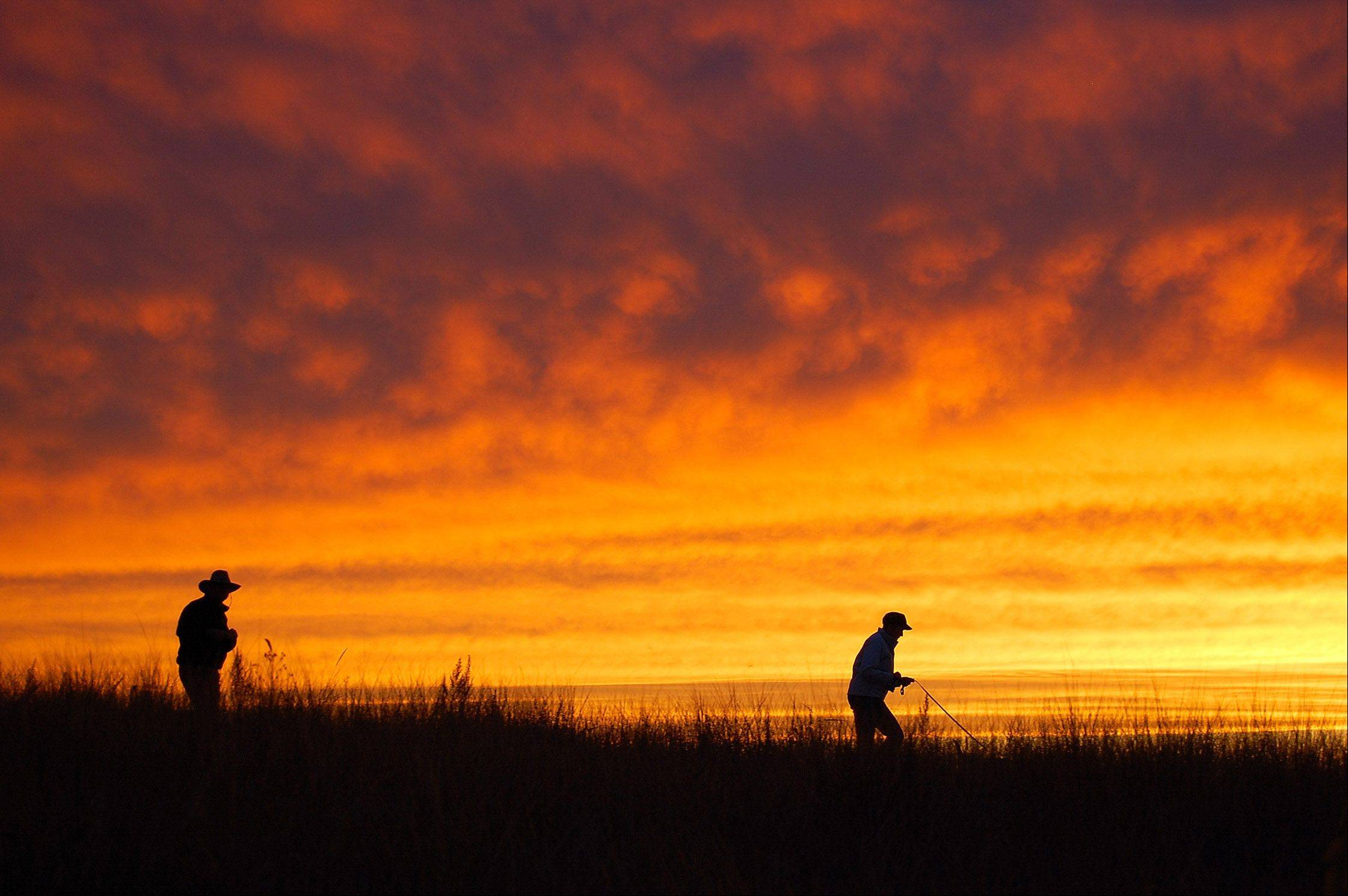 A couple walk their dog in the beach grass along Lake Michigan in Leland, Michigan last month.