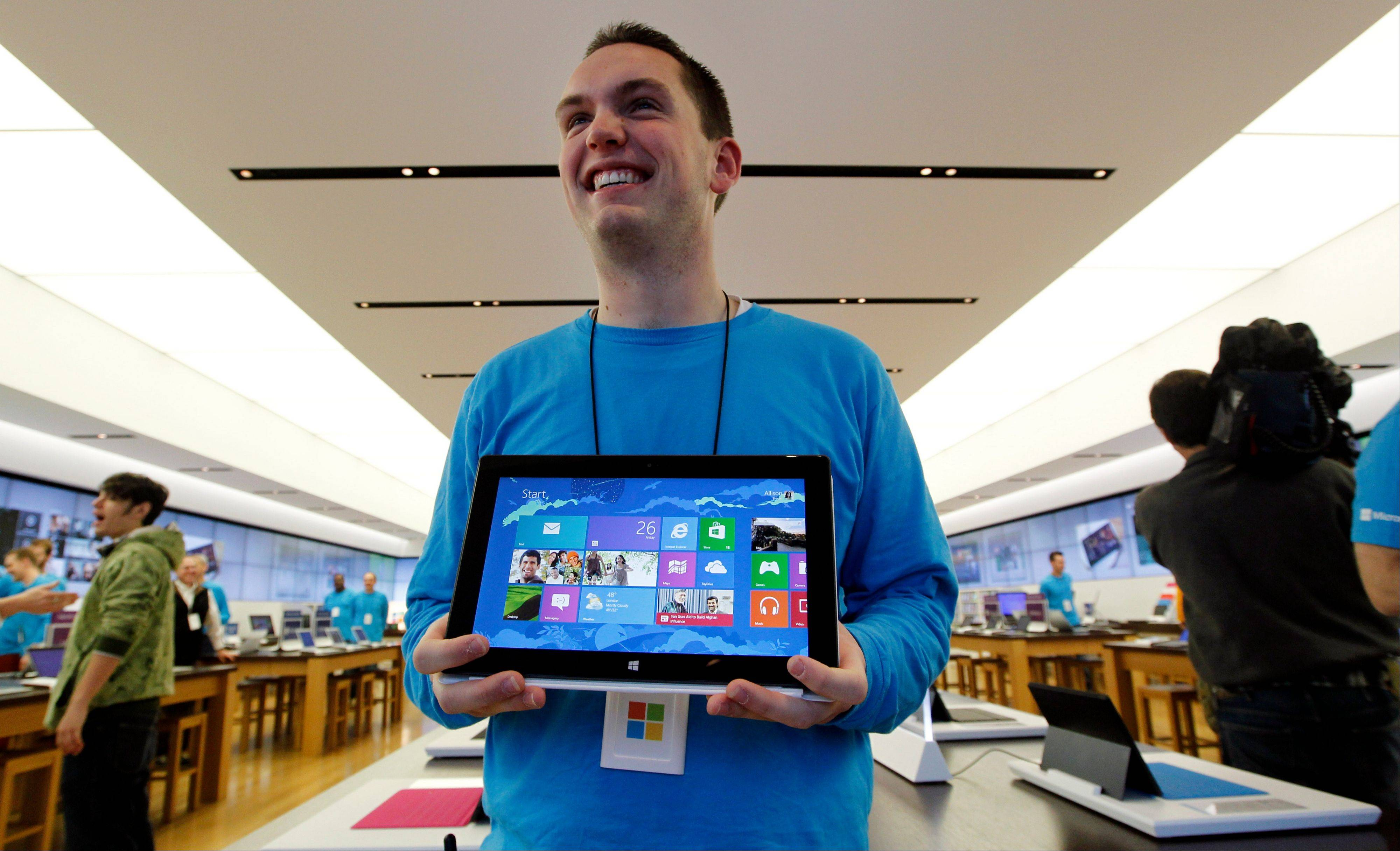Microsoft store product adviser Stuart Pitts displays the new Surface tablet computer as customers enter the Seattle store on Friday.