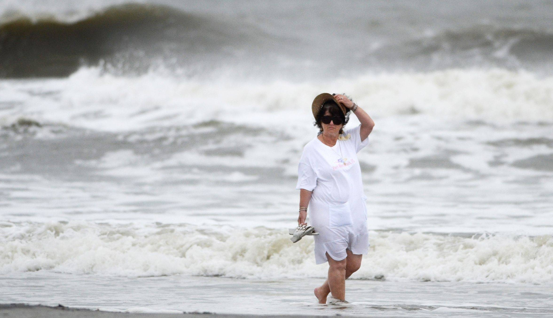 A beach goer holds on to her hat as she walks along a breezy Coligny Beach Park Saturday on Hilton Head Island, S.C., watching the waves generated by Hurricane Sandy near the time of high tide. Hurricane Sandy — upgraded again Saturday just hours after forecasters said it had weakened to a tropical storm — was barreling north from the Caribbean.