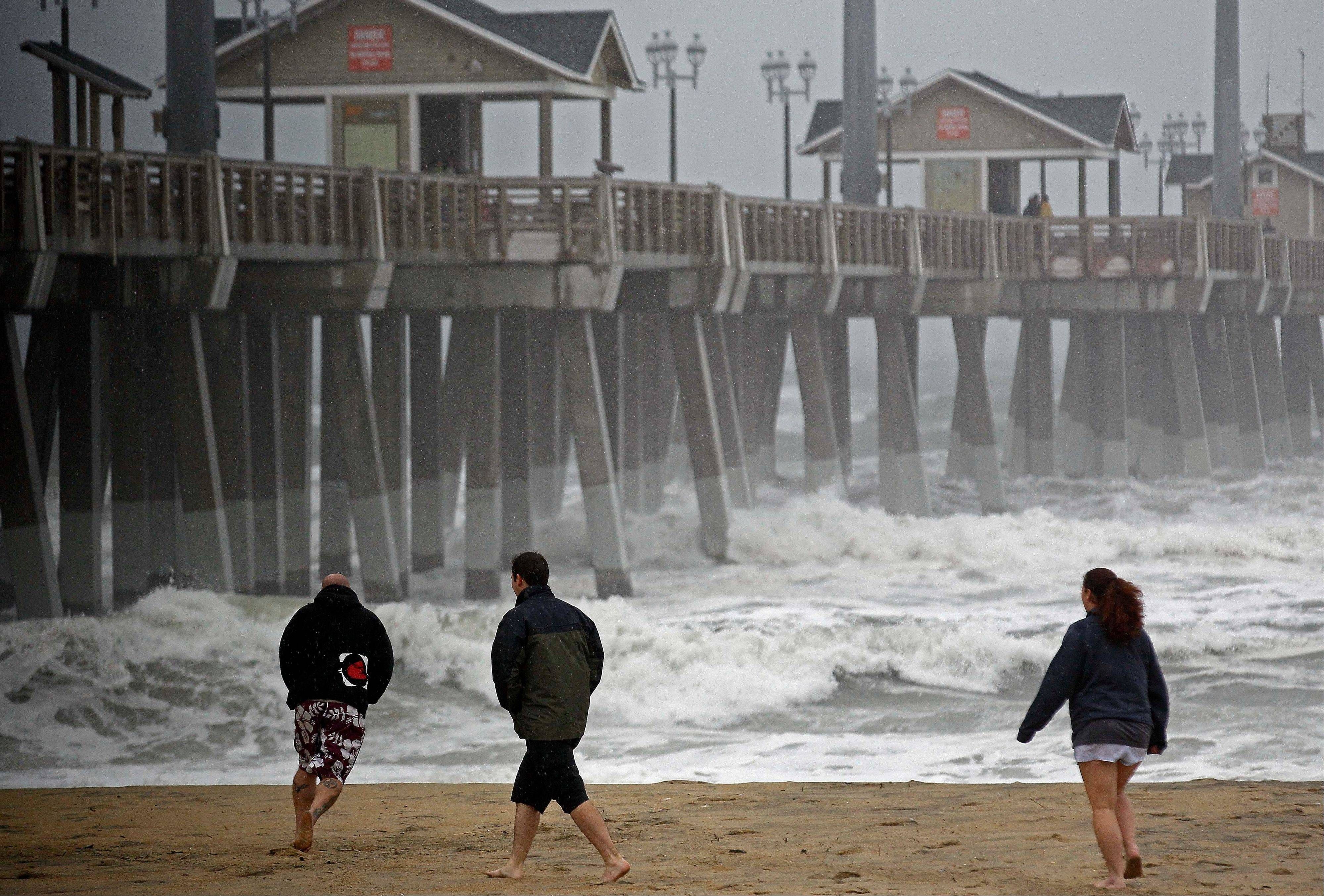 Beachgoers walk in the wind and rain as waves generated by Hurricane Sandy crash into Jeanette's Pier in Nags Head, N.C., Saturday, Oct. 27, 2012, as the storm churns up the east coast. Hurricane Sandy, upgraded again Saturday just hours after forecasters said it had weakened to a tropical storm, was barreling north from the Caribbean and was expected to make landfall early Tuesday.