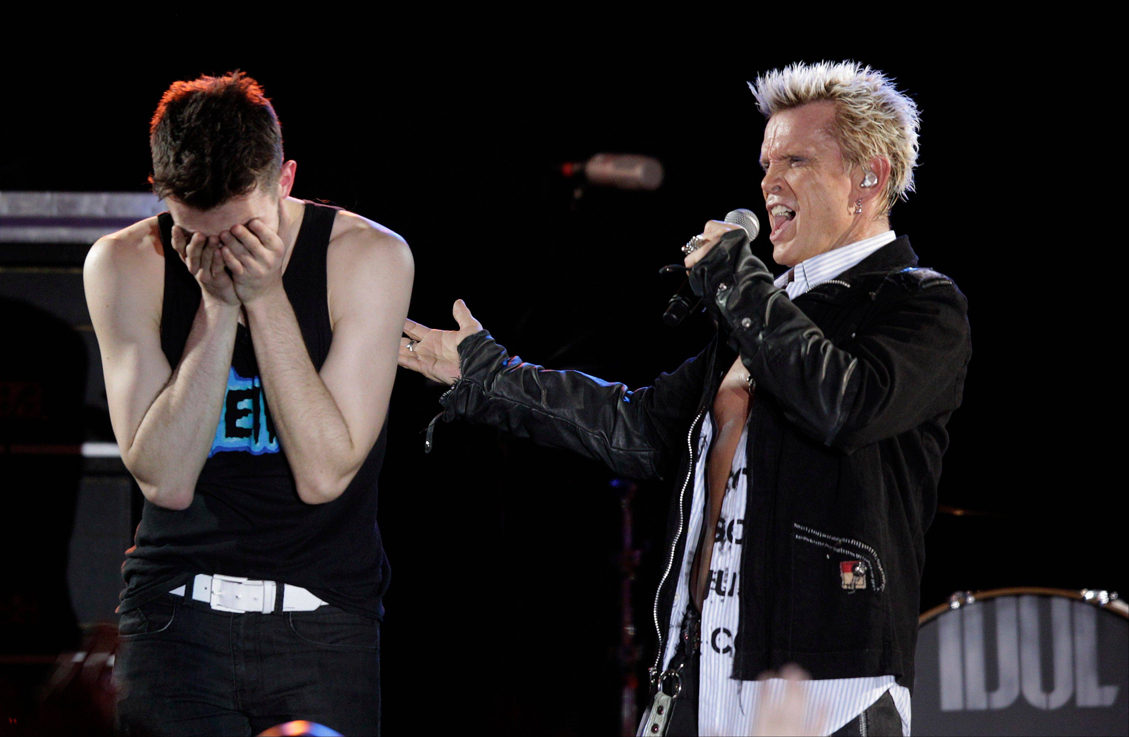 Billy Idol, right, is joined on stage by Michael Henrichsen, left, as Idol performs Friday in Seattle.