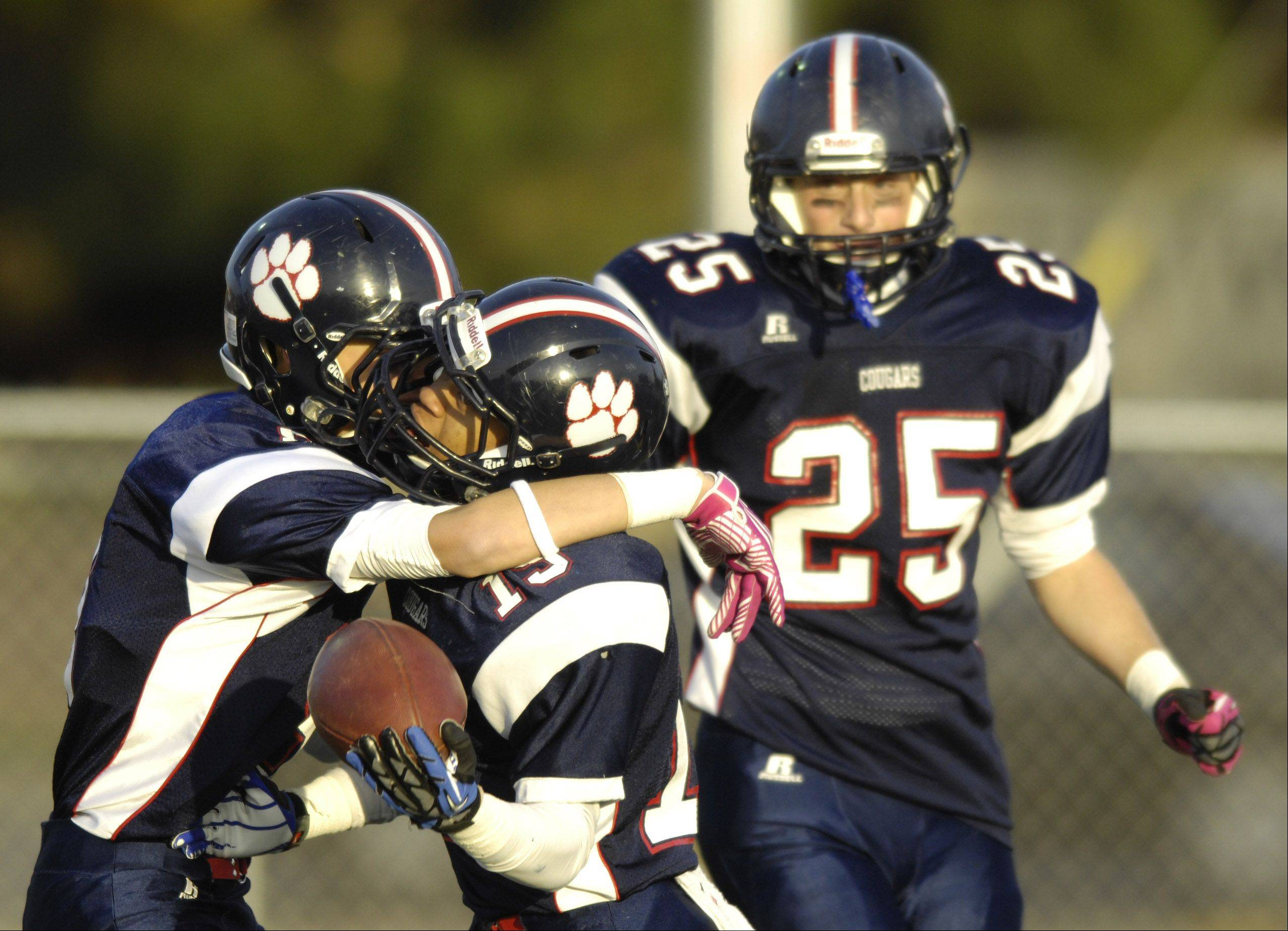 Conant's Bryson Brown, center, celebrates his fourth-quarter touchdown with teammates Zach Smith, left, and Mike Kos during Saturday's 14-0 win over New Trier.