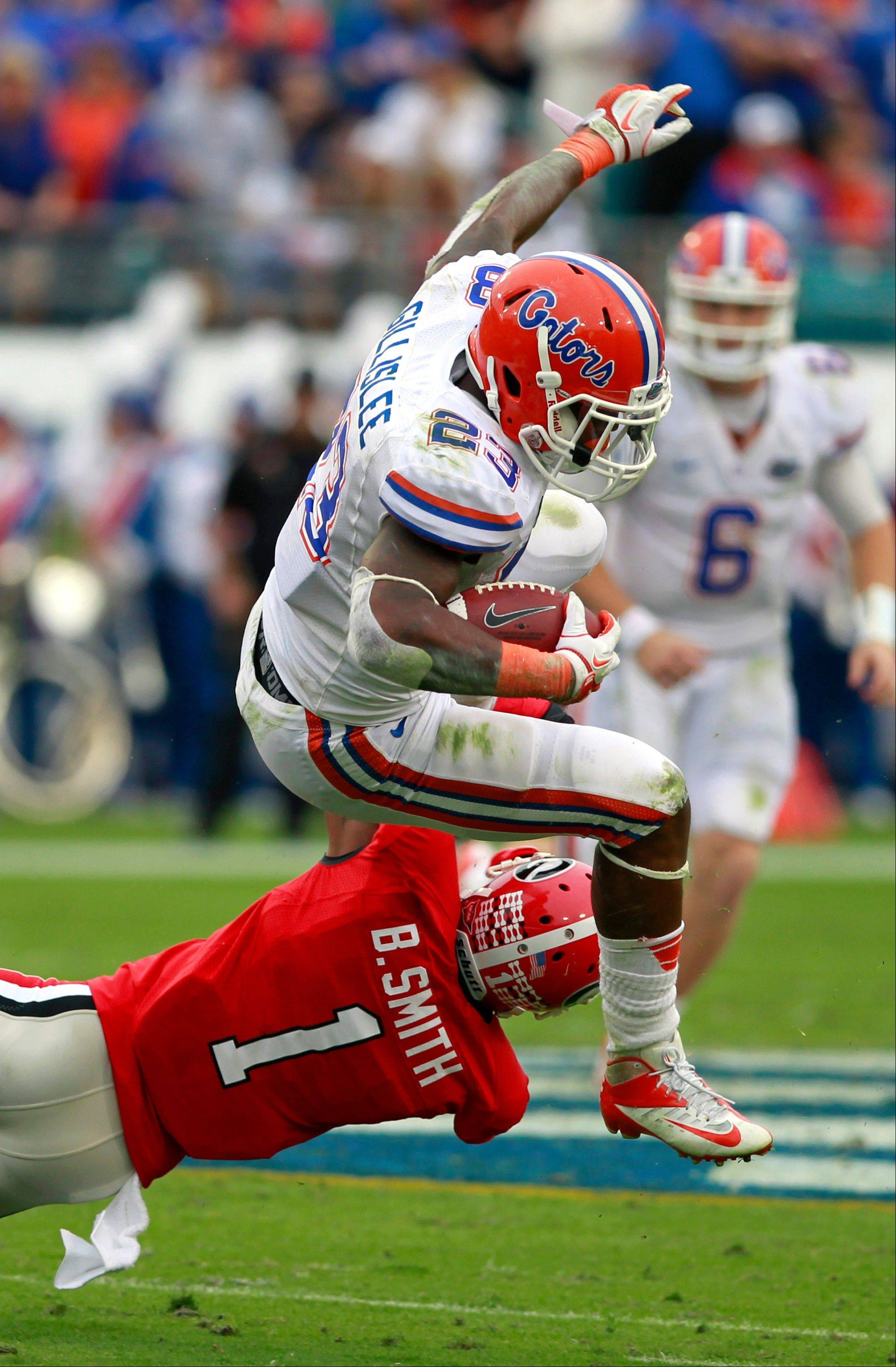 Florida running back Mike Gillislee (23) is upended by Georgia cornerback Branden Smith (1) during the first half of an NCAA college football game on Saturday, Oct. 27, 2012, in Jacksonville, Fla. (AP Photo/John Raoux)