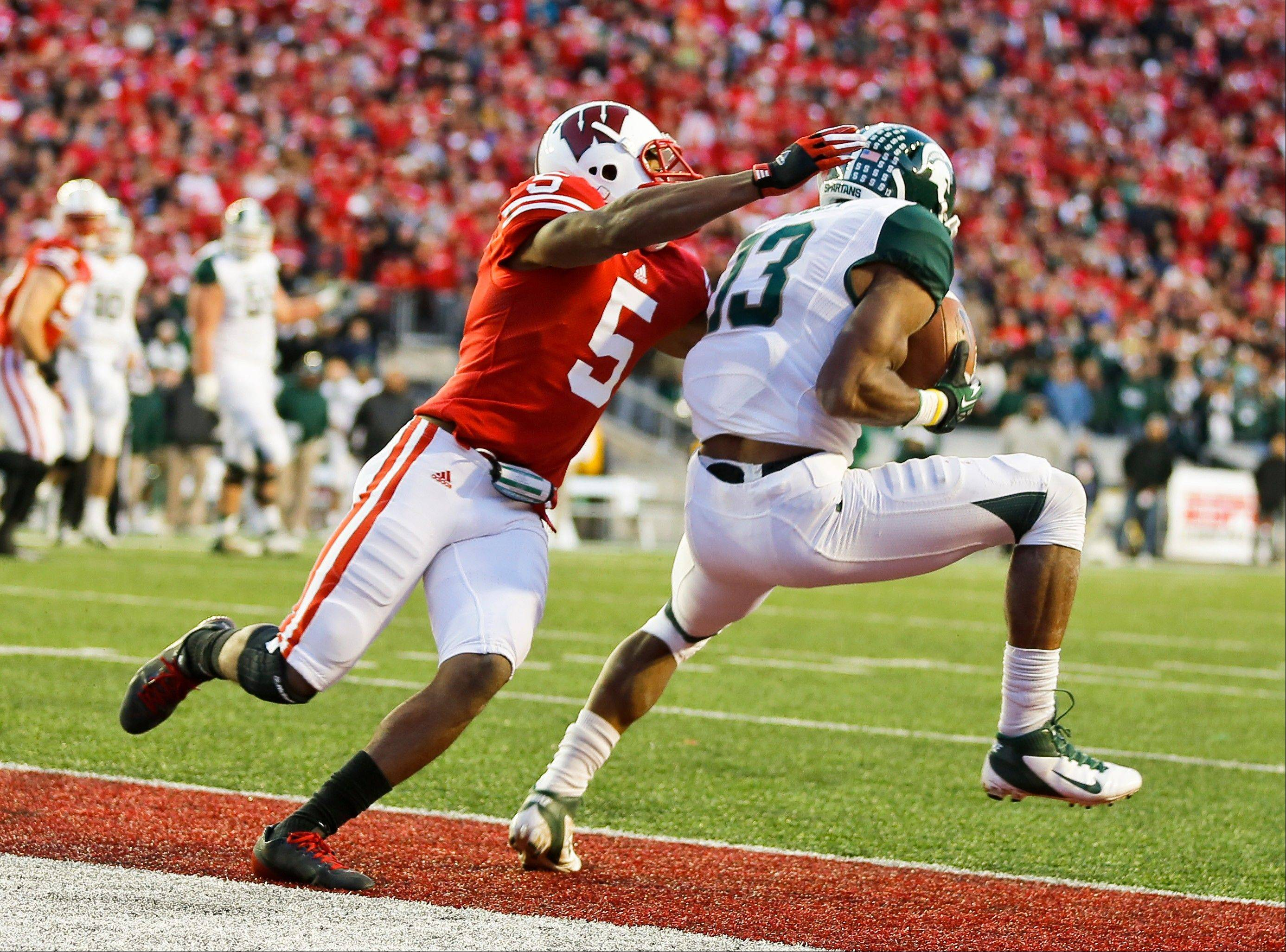 Michigan State wide receiver Bennie Fowler (13) makes the game-winning touchdown catch against Wisconsin defensive back Darius Hillary (5) in overtime in an NCAA college football game Saturday, Oct. 27, 2012, in Madison, Wis. Michigan State won 16-13. (AP Photo/Andy Manis)