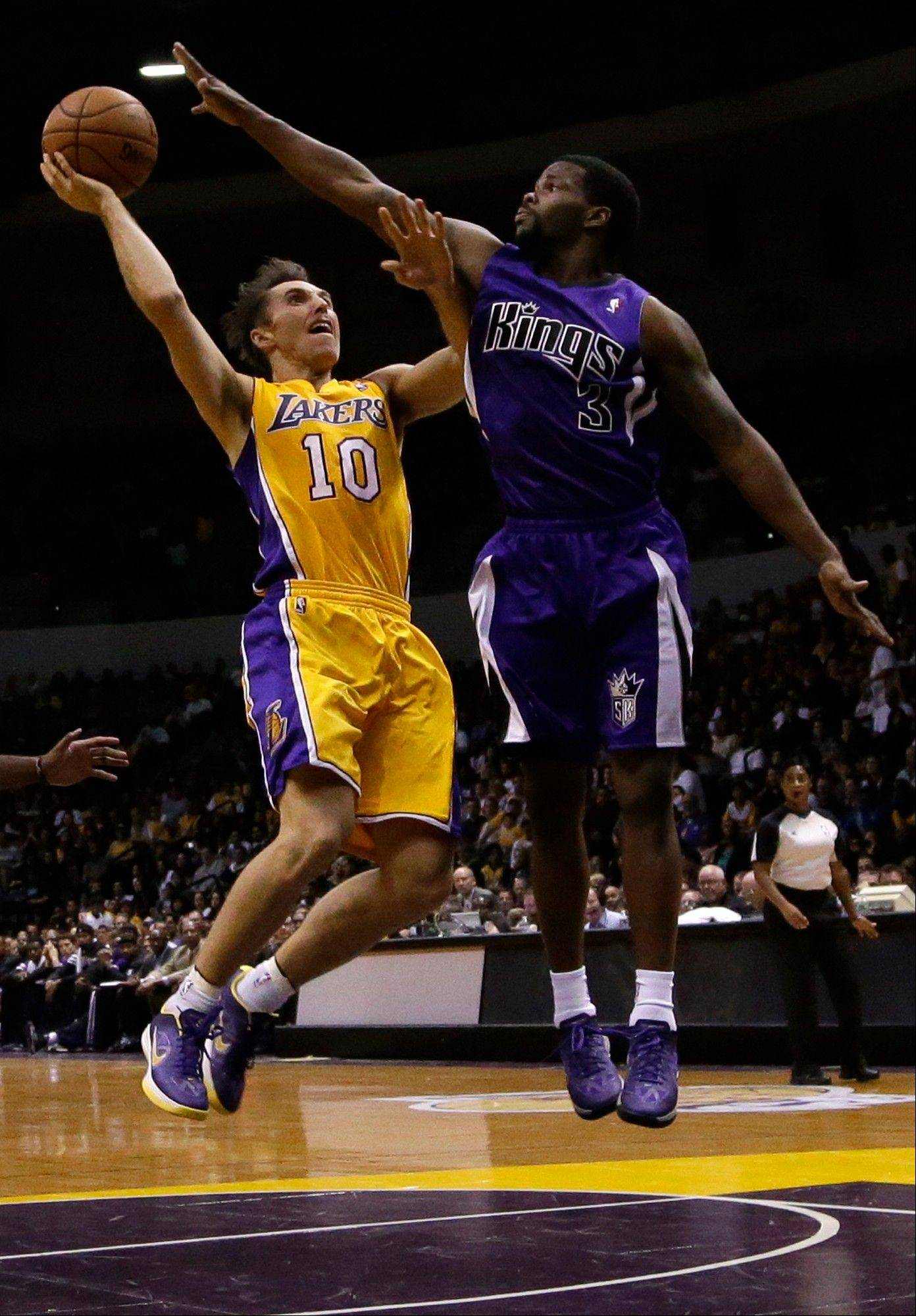 Los Angeles Lakers point guard Steve Nash, left, shoots as Sacramento Kings point guard Aaron Brooks defends during a preseason game on Thursday.