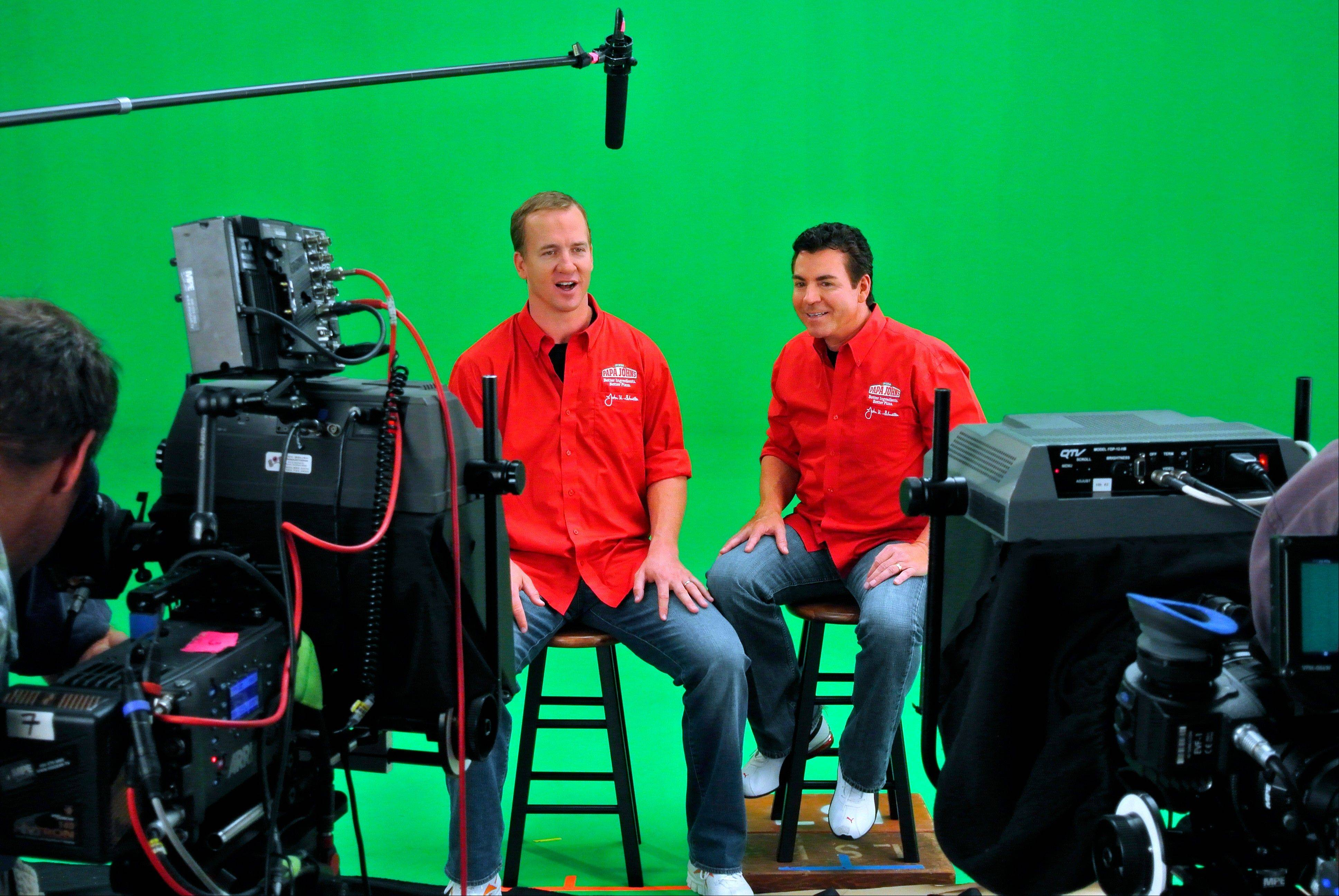 In this photo released by Papa John's on Friday, Denver Broncos quarterback Peyton Manning, left, shoots a television spot with Papa John's founder John Schnatter. In the ad, Manning reveals he is Papa John's latest franchisee.