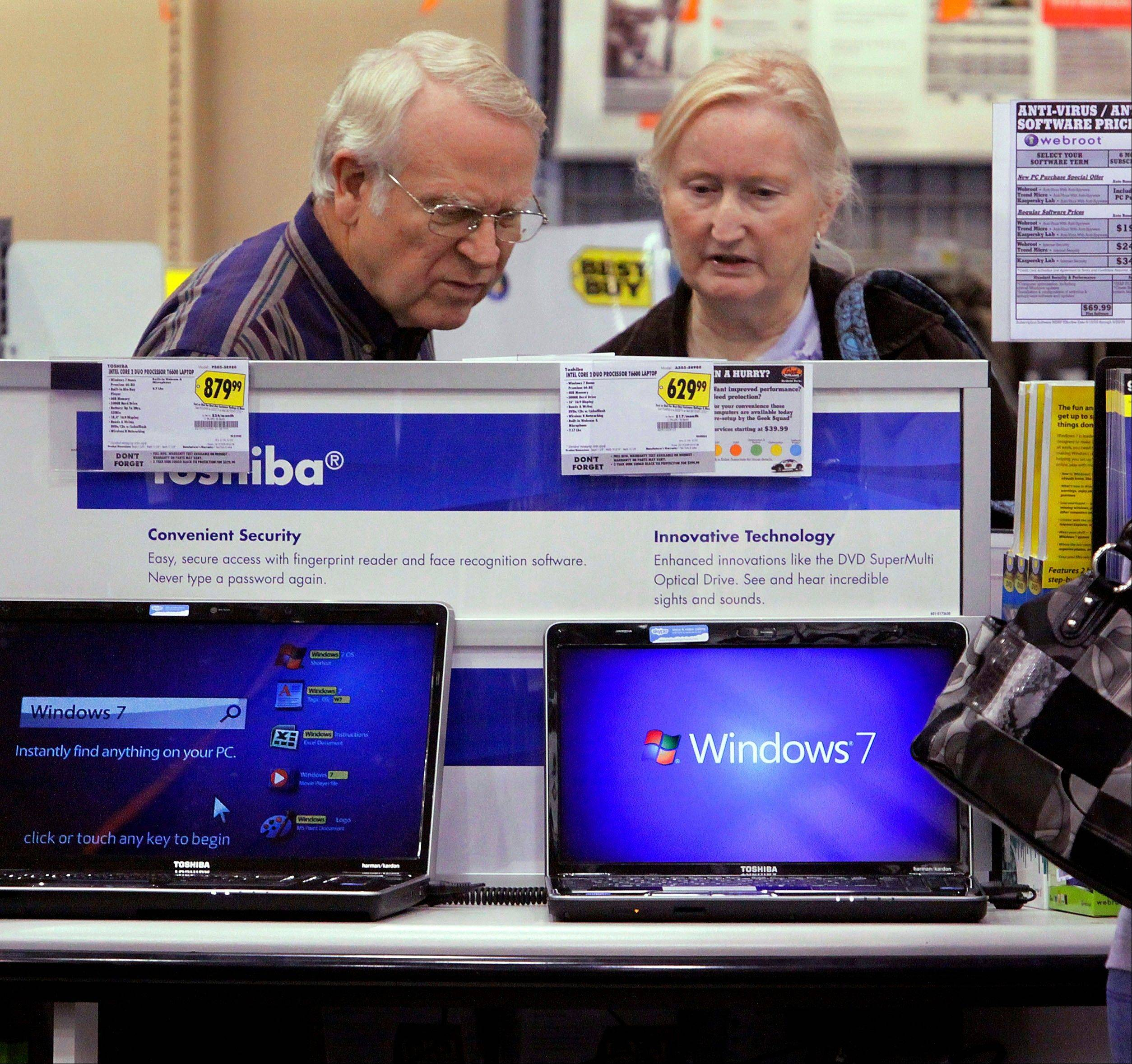 Computer shoppers read through options and compare prices at a Best Buy in Springfield. after Microsoft launched Windows 7. Best Buy is hoping to capitalize on the launch of Windows 8. It's trying to lure customers with exclusive computers and staffers trained to explain and demonstrate the new operating system from Microsoft Corp.