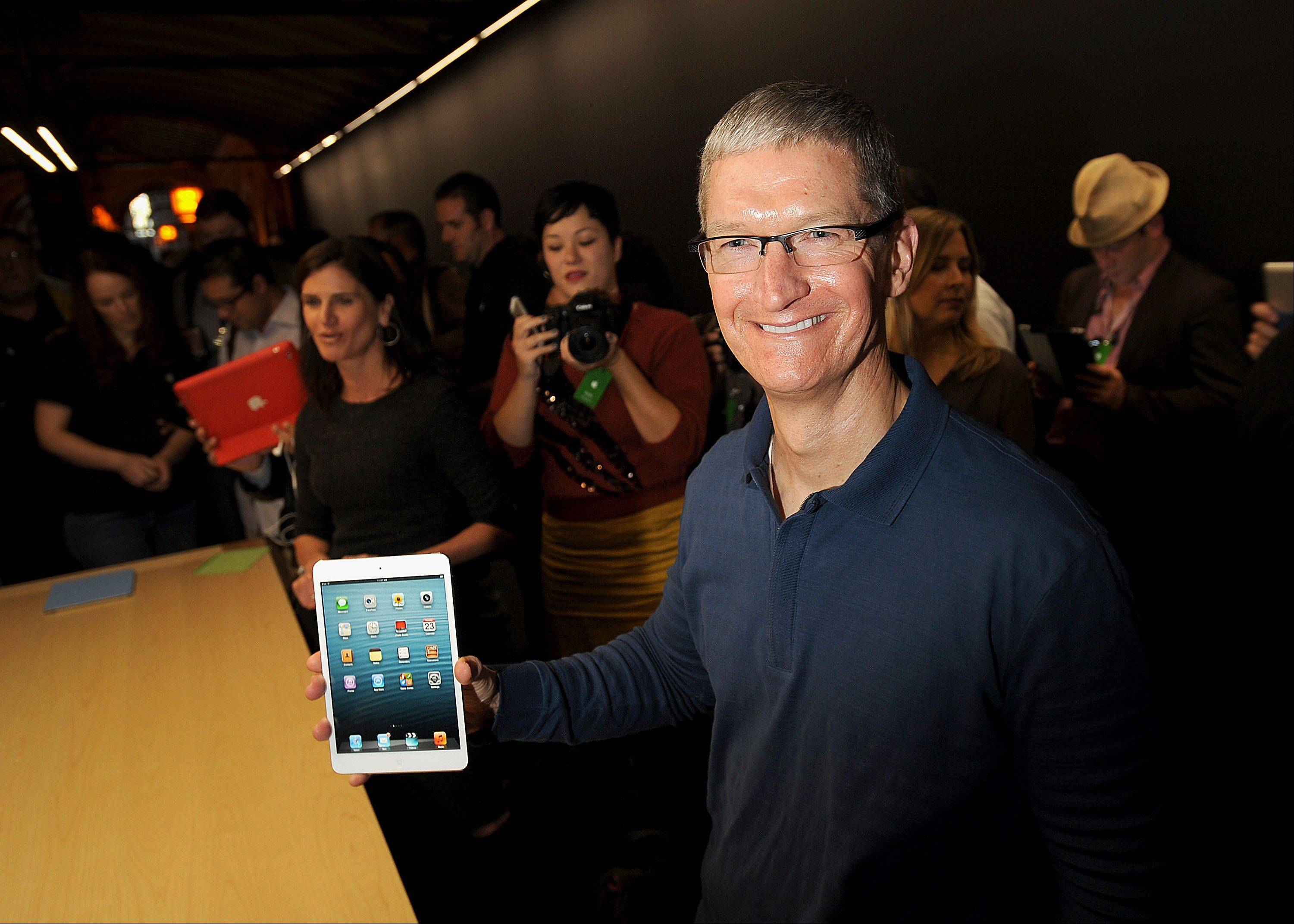 Tim Cook, chief executive officer of Apple Inc., holds an iPad Mini Tuesday during an event in San Jose, California. Apple Inc. introduced a smaller version of the iPad designed to keep customers from buying low-cost tablets from competitors Microsoft Corp., Amazon.com Inc. and Google Inc.