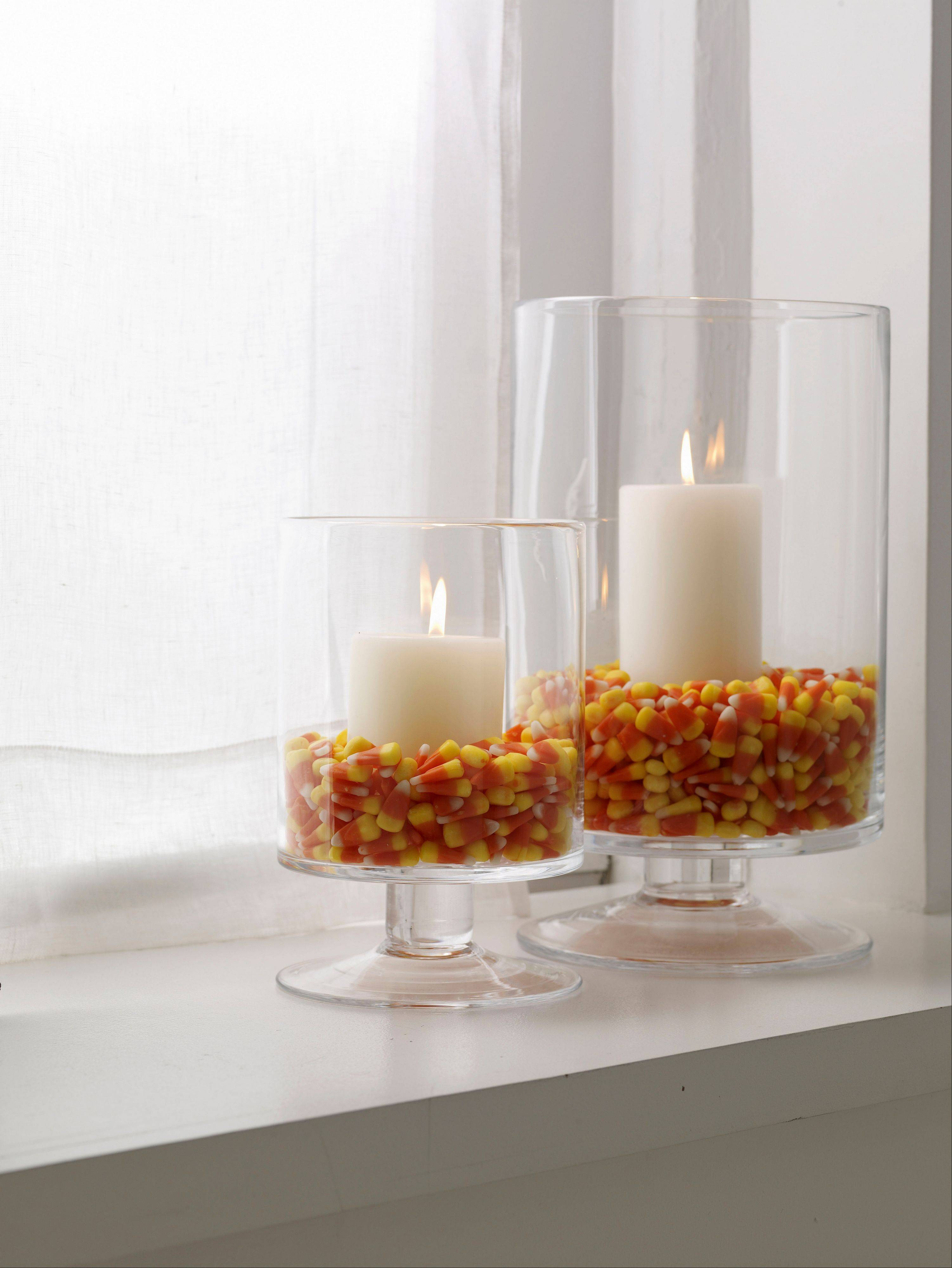 Glass hurricanes filled with colorful candy corn and nestled pillar candles make an interesting tabletop display, as suggested by Woman's Day magazine's craft editors.