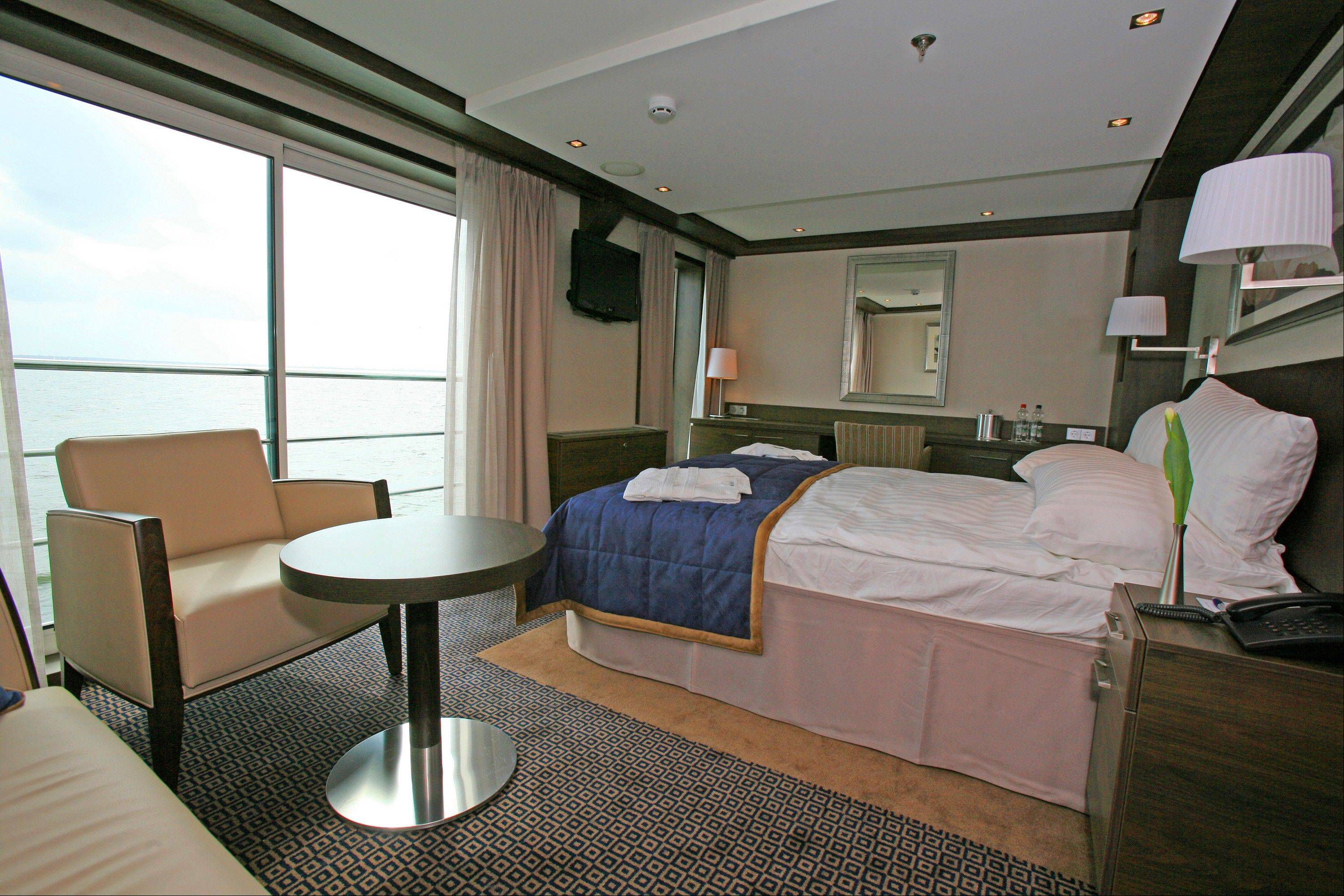 The interior of a suite, features a sliding glass door and french balcony on the river ship Avalon Felicity.