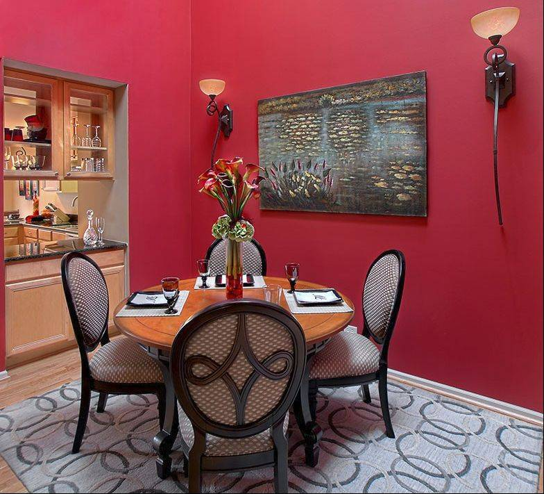 "The dining area makes a bold use of red, and brings in a flavor of the outdoors with the ""lily pond"" painting."
