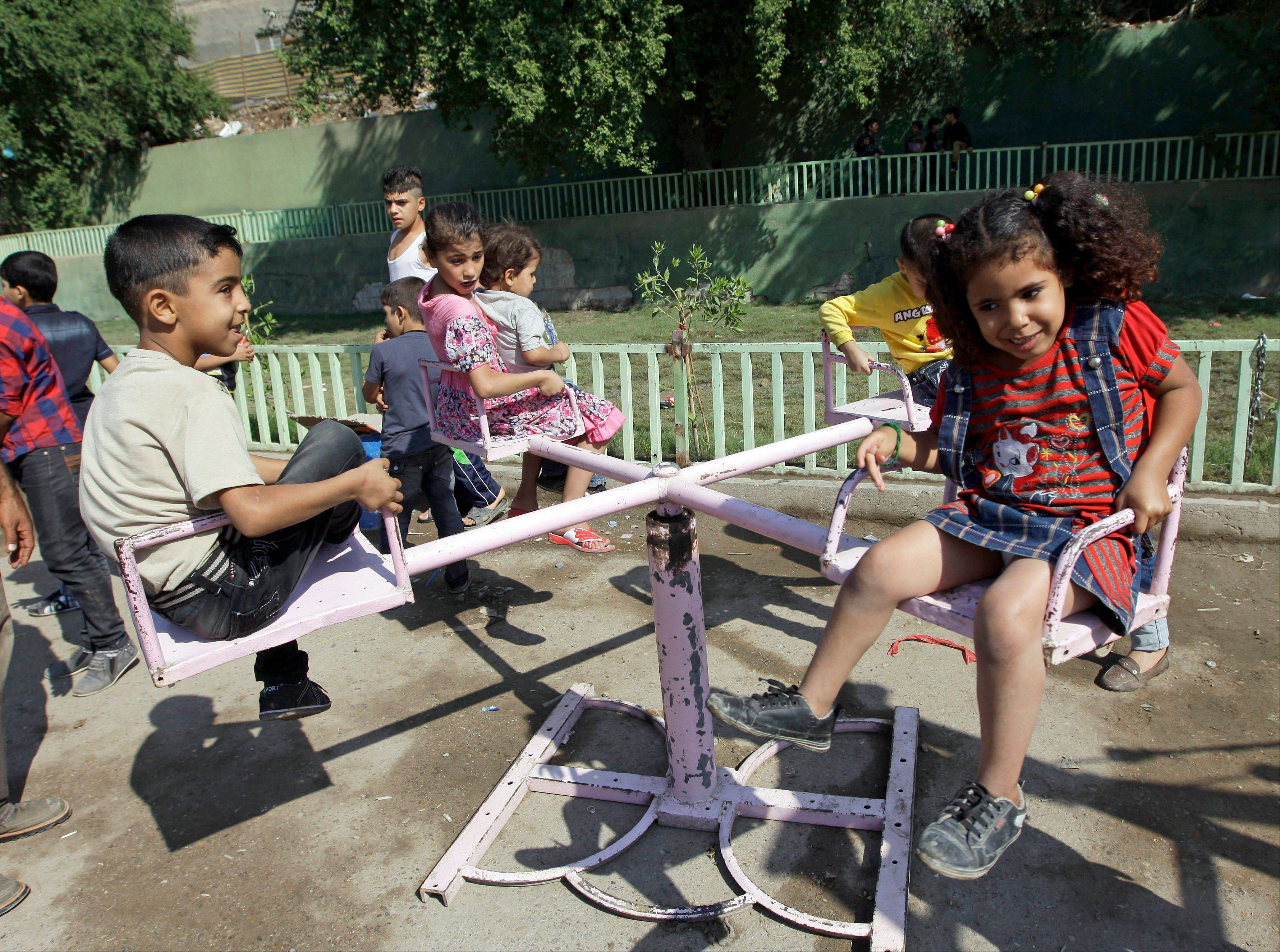 Iraqi children play during Eid al-Adha celebrations Saturday in Baghdad's Fadhil neighborhood, Iraq. A bombing near a playground and other insurgent attacks killed 31 people including several children in Iraq on Saturday.