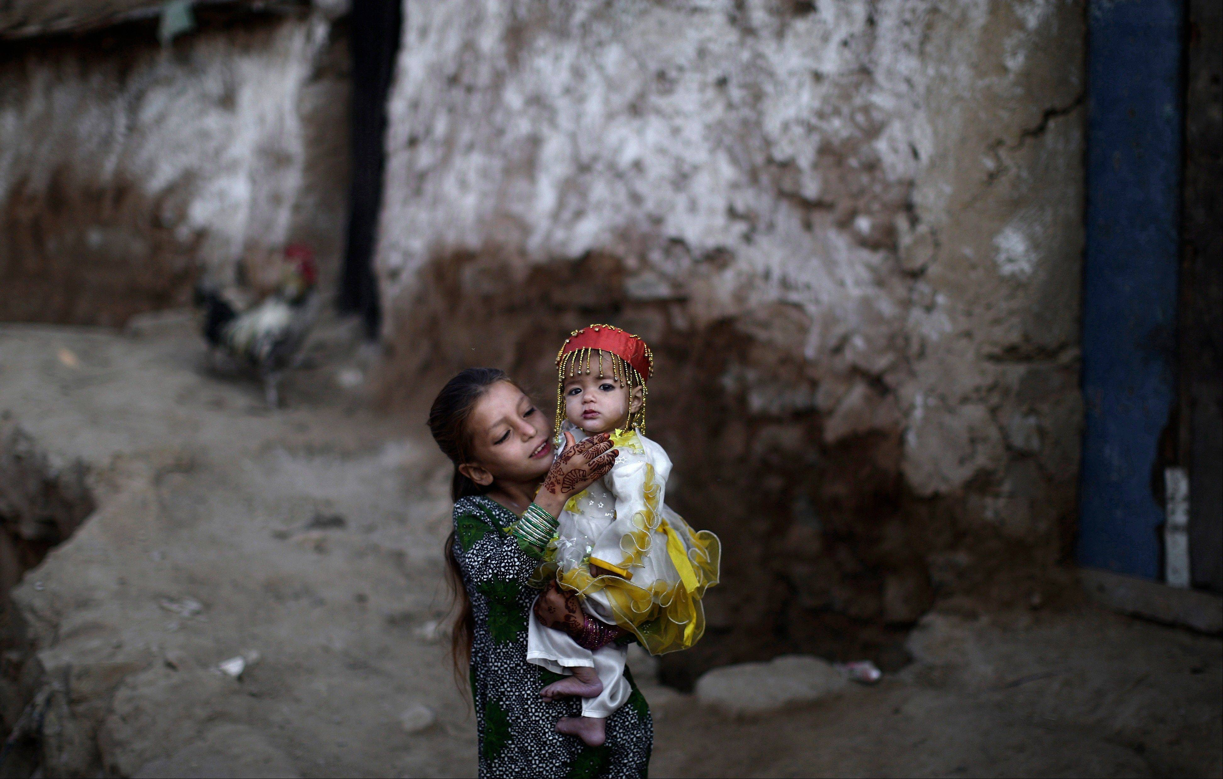 "Associated Press Afghan refugee girl Parveen Bashir, 6, plays Saturday with her sister Shaheen, 1, dressed in new clothes, while celebrating the first day of the Muslim holiday of Eid al-Adha, or ""Feast of Sacrifice"", on the outskirts of Islamabad, Pakistan."