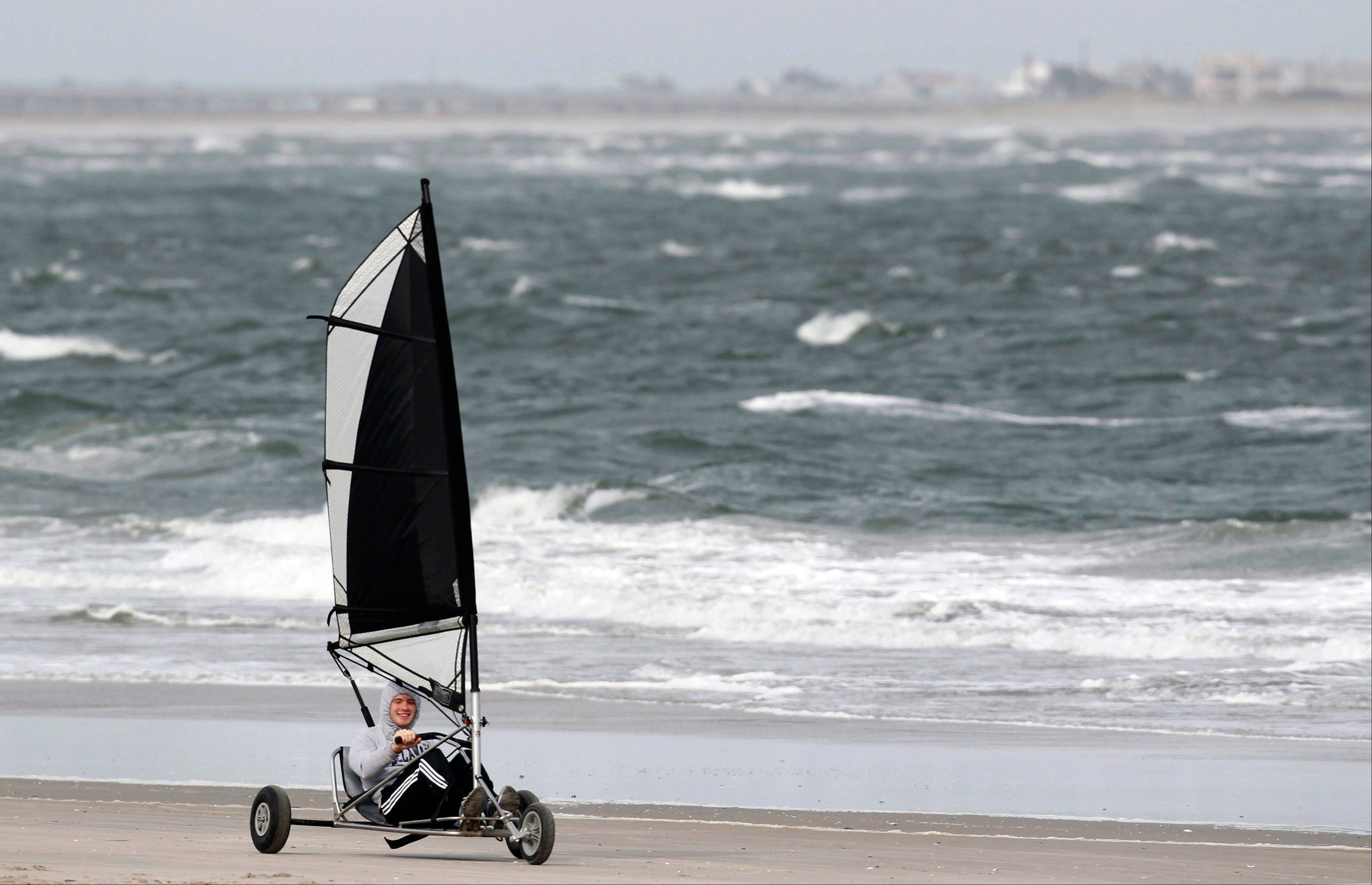 A person rides in a cart blown by the winds along the Altlantic Ocean in North Wildwood, N.J., Saturday, Oct. 27, 2012, as the winds pick up ahead of Hurricane Sandy. From the lowest lying areas of the Jersey shore, where residents were already being encouraged to leave, to the state's northern highlands, where sandbags were being filled and cars moved into parking lots on high ground, New Jersey began preparing in earnest for Hurricane Sandy.