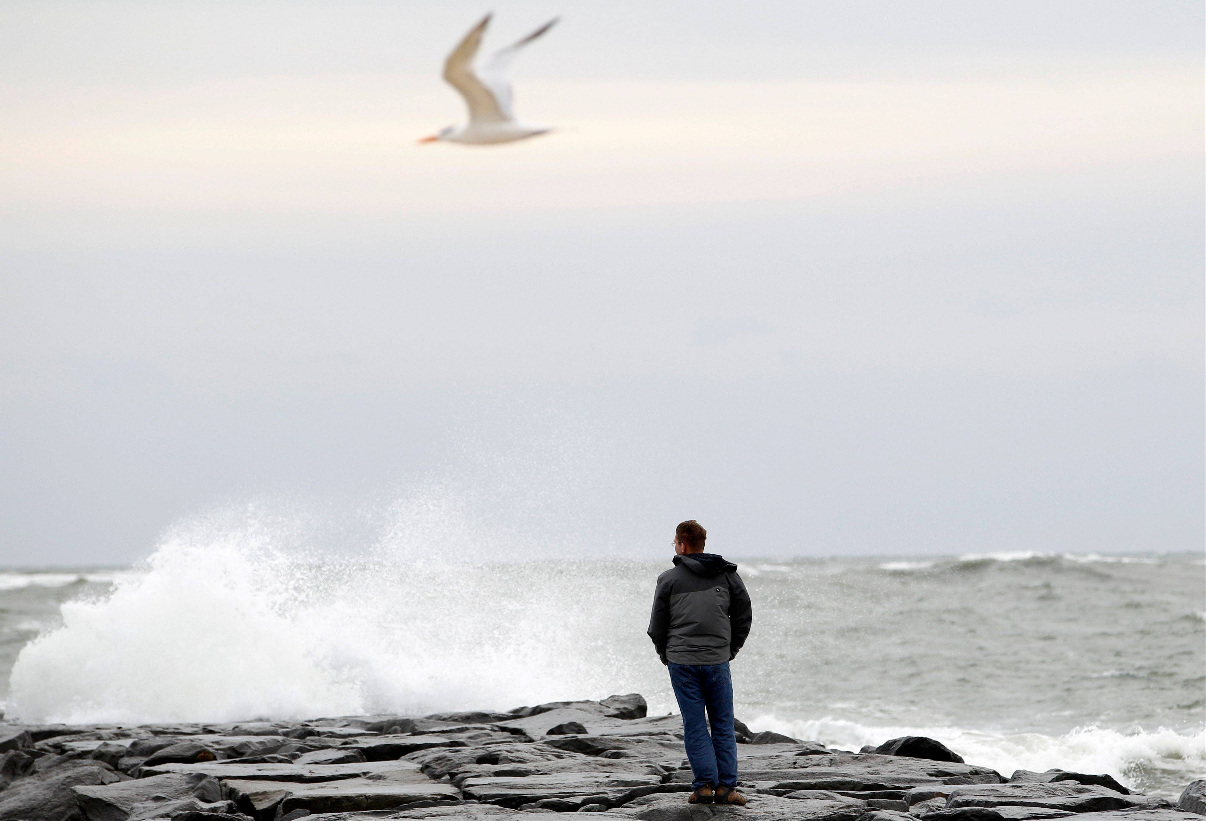 Resident Brian Dougherty looks at the waves from the beach in Ocean City, Md., as Hurricane Sandy approaches the Atlantic Coast, on Saturday, Oct. 27, 2012.