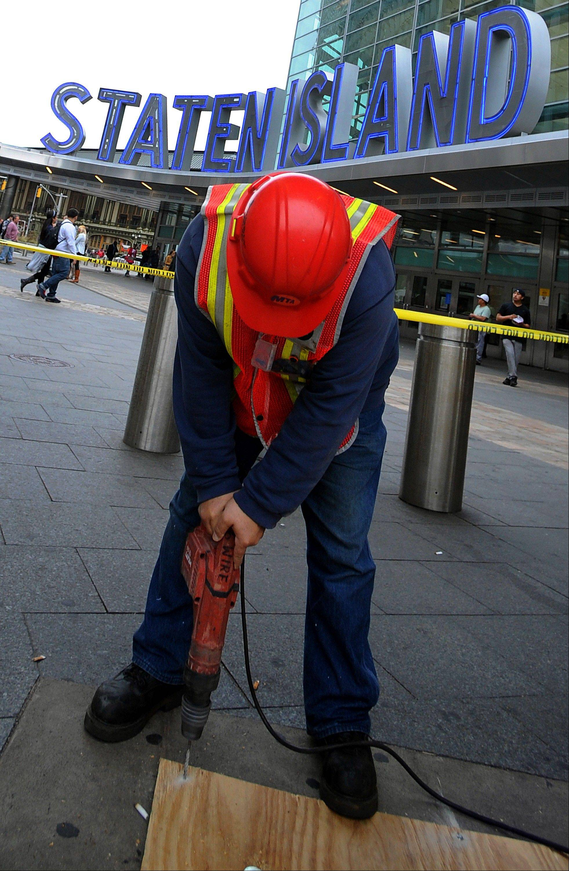 A Metropolitan Transit Authority worker lays down plywood over subway grates at the Staten Island Ferry Terminal to prevent flooding in New York, U.S., on Friday, Oct. 26, 2012. New York City officials discussed plans for evacuations and subway closings to deal with Hurricane Sandy as Governor Andrew Cuomo declared a state of emergency in all of the state�s 62 counties.