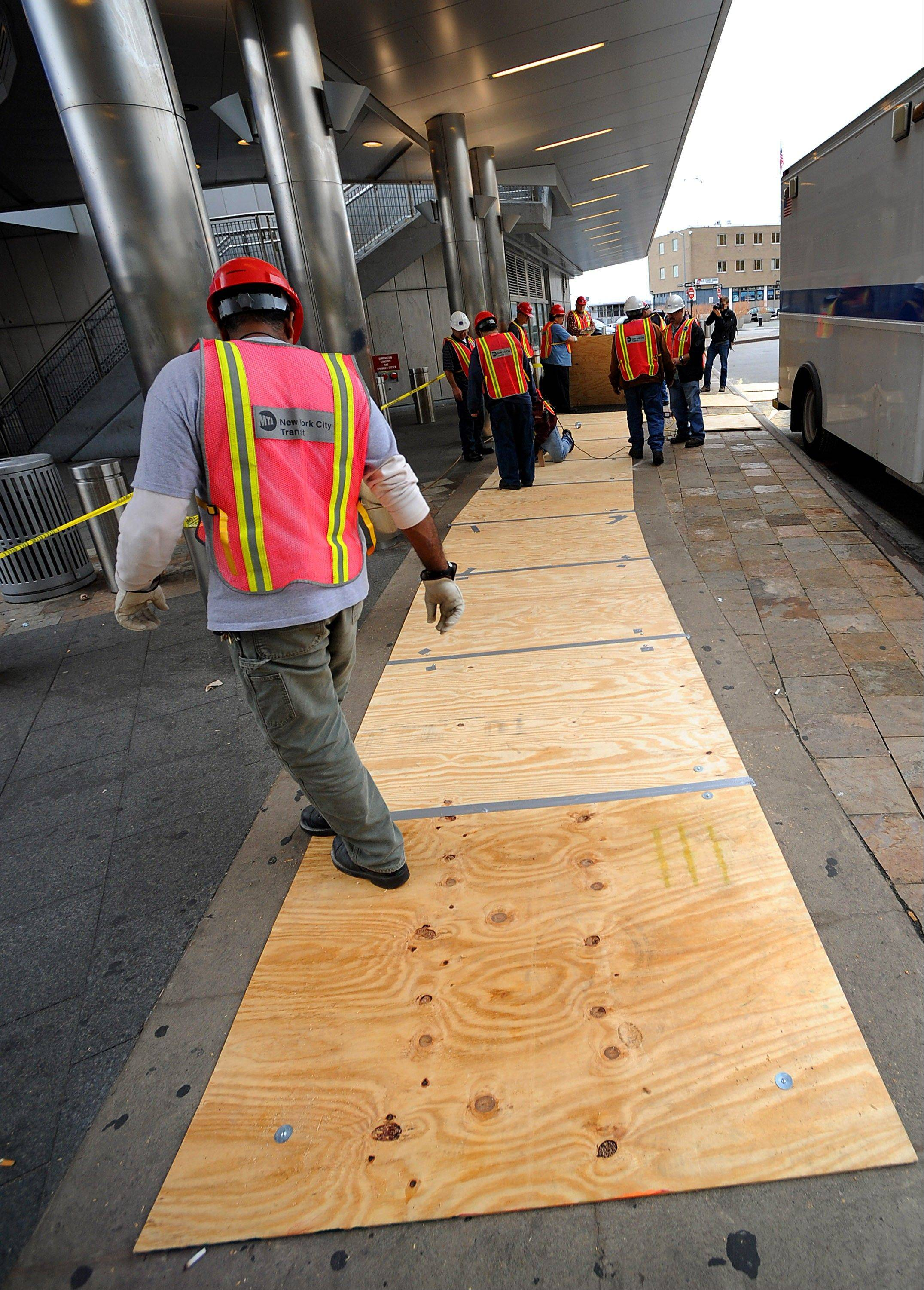 Metropolitan Transit Authority workers lay down plywood over subway grates at the Staten Island Ferry Terminal to prevent flooding in New York, U.S., on Friday, Oct. 26, 2012. New York City officials discussed plans for evacuations and subway closings to deal with Hurricane Sandy as Governor Andrew Cuomo declared a state of emergency in all of the state�s 62 counties.
