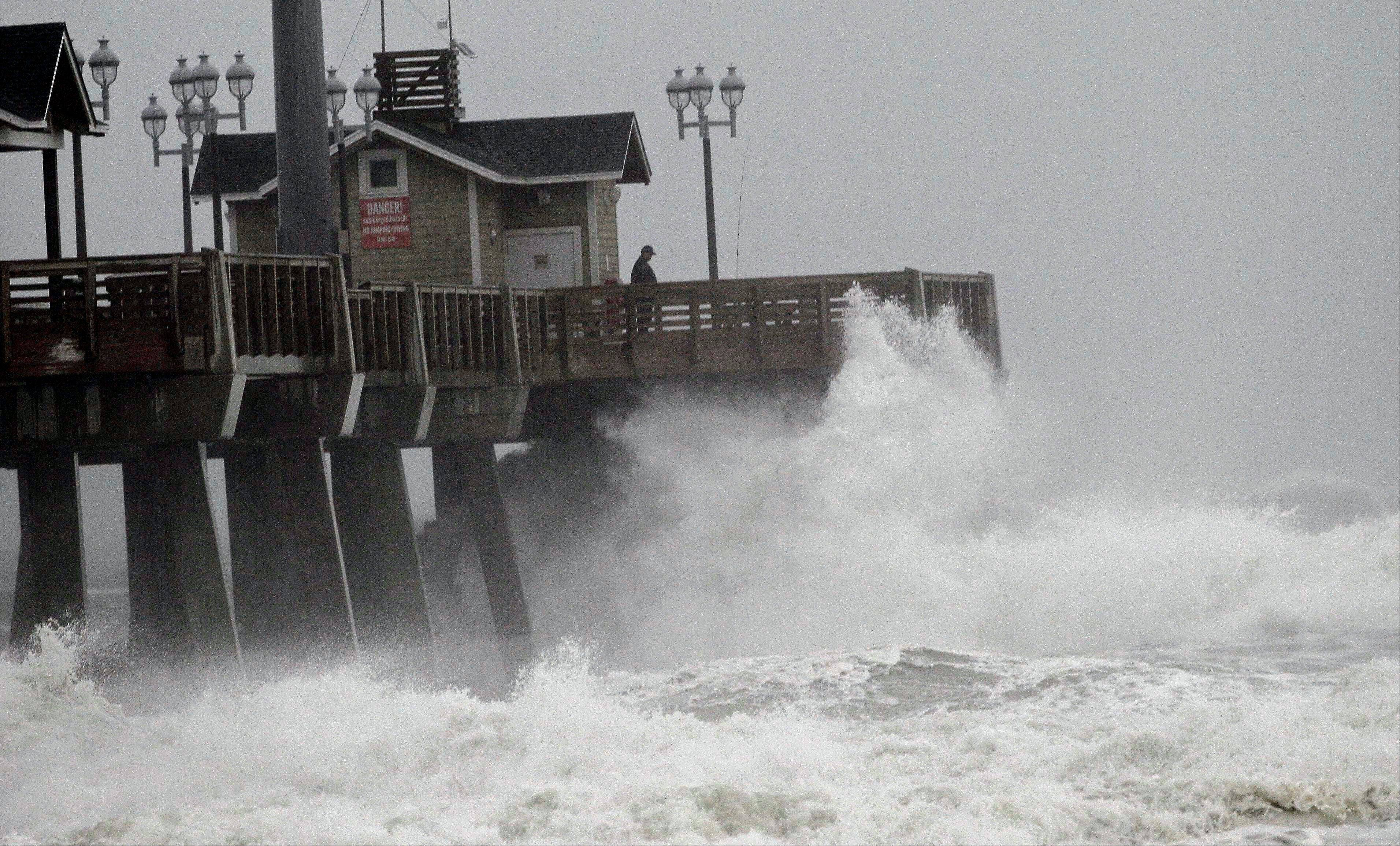 Large waves generated by Hurricane Sandy crash into Jeanette's Pier in Nags Head, N.C., Saturday, Oct. 27, 2012 as the storm moves up the east coast. Hurricane Sandy, upgraded again Saturday just hours after forecasters said it had weakened to a tropical storm, was barreling north from the Caribbean and was expected to make landfall early Tuesday near the Delaware coast.
