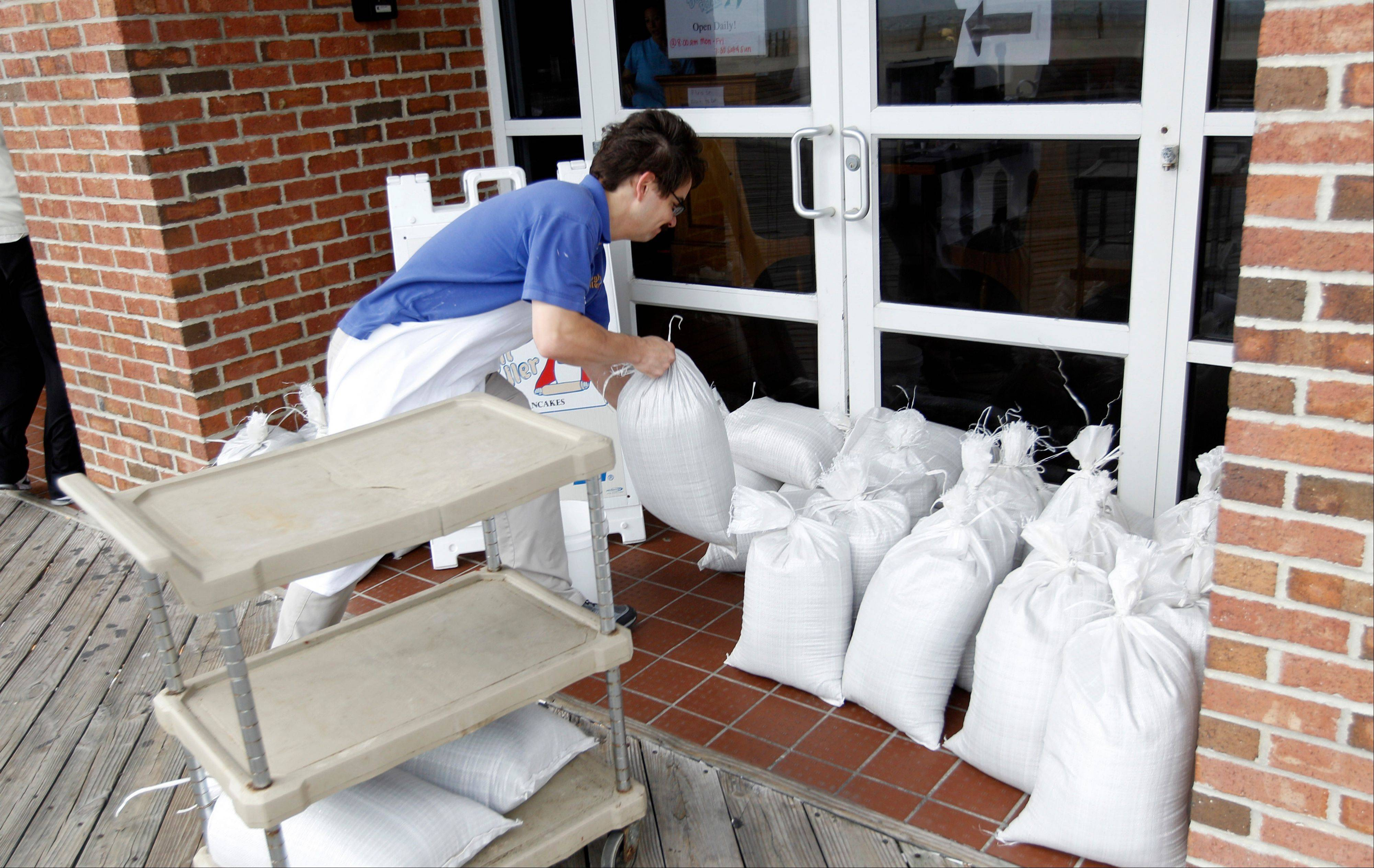 A restaurant worker piles sand bags at the entrance of the business as Hurricane Sandy approaches the Atlantic Coast, in Ocean City, Md., on Saturday, Oct. 27, 2012.