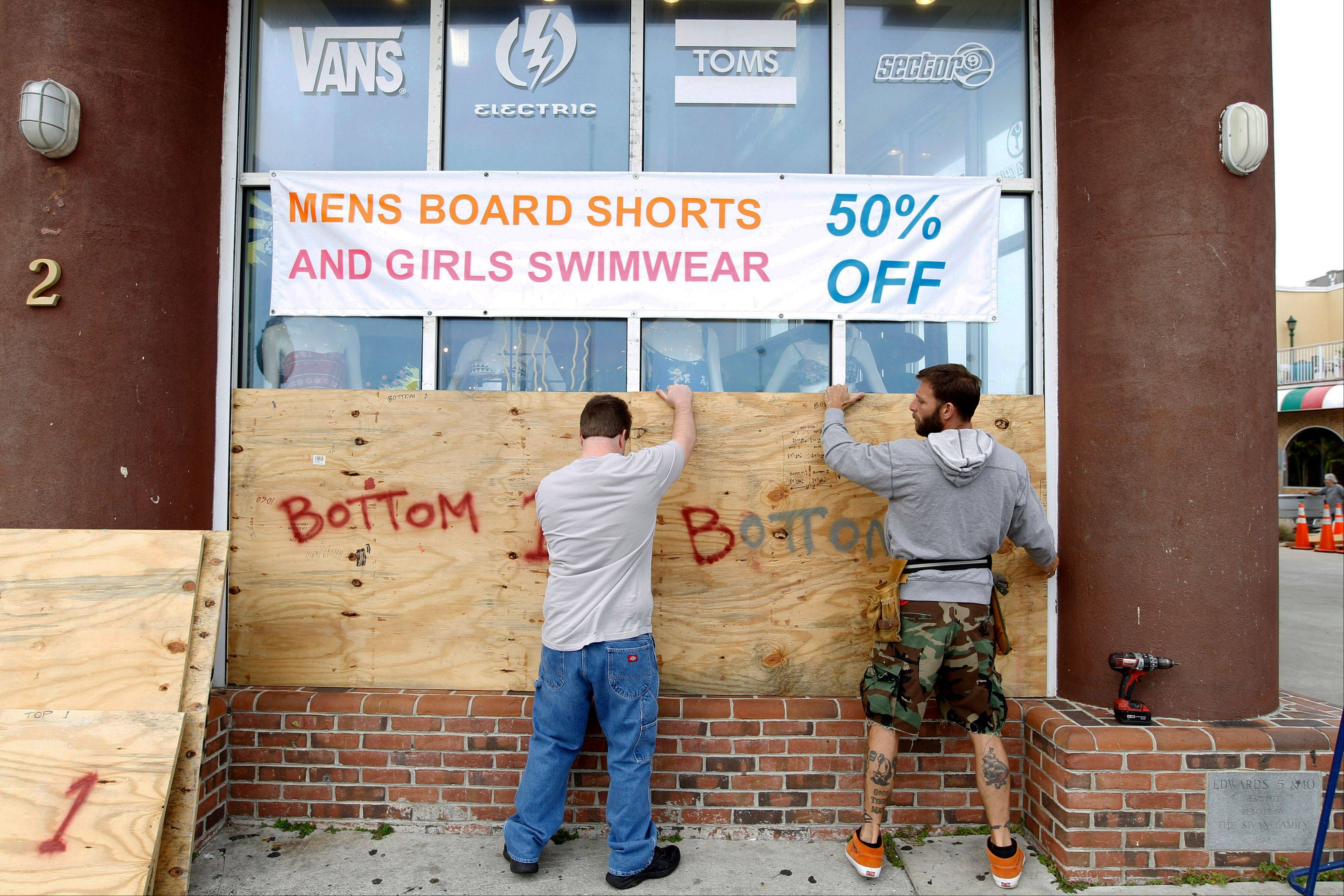 Store manager L.P. Cyburt, right, gets help boarding up the windows of the business as Hurricane Sandy approaches the Atlantic Coast, in Ocean City, Md., on Saturday, Oct. 27, 2012.