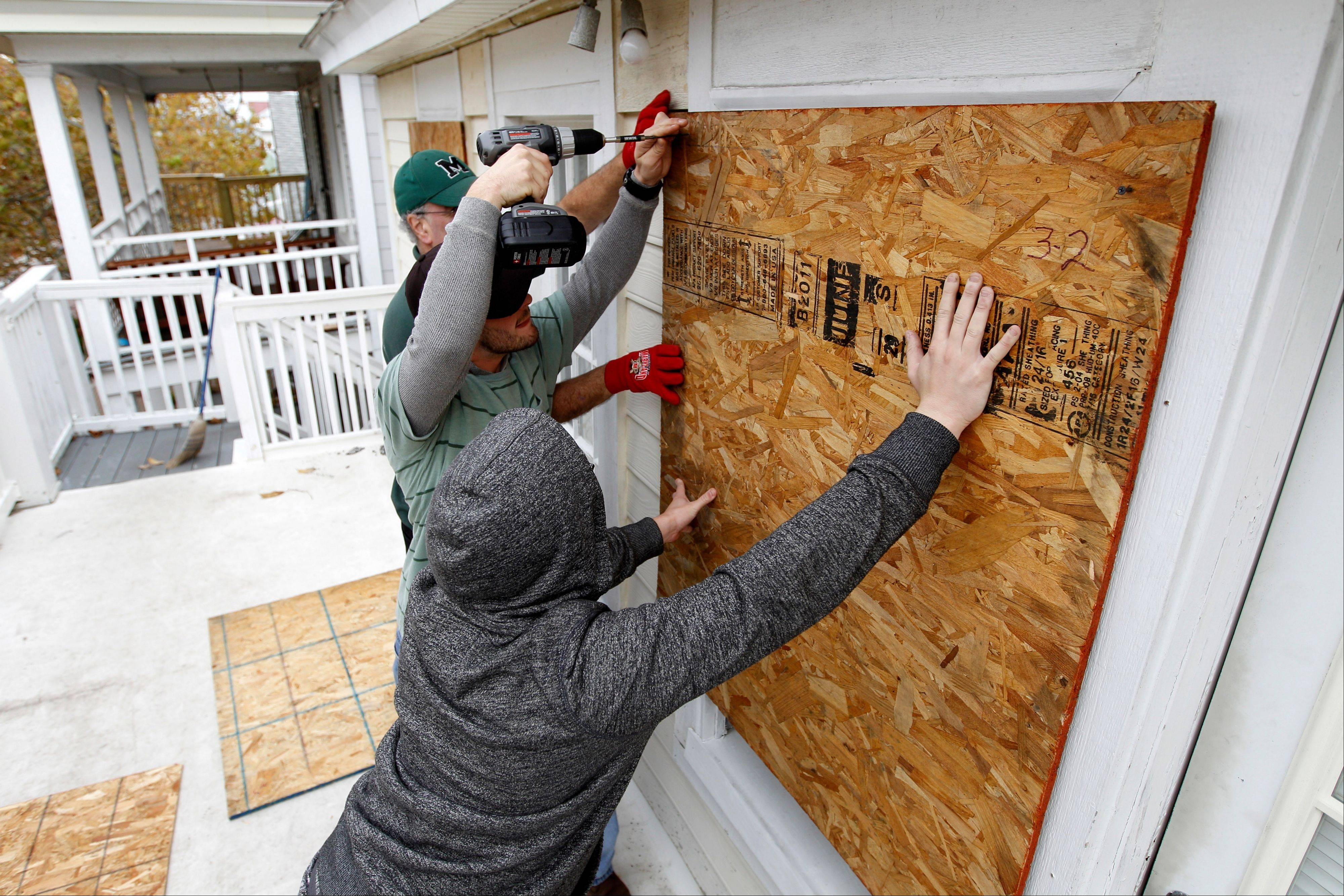 Scott Viviano, holding the drill, helps his friends to board up the windows of their home as Hurricane Sandy approaches the Atlantic Coast, in Ocean City, Md., on Saturday, Oct. 27, 2012.