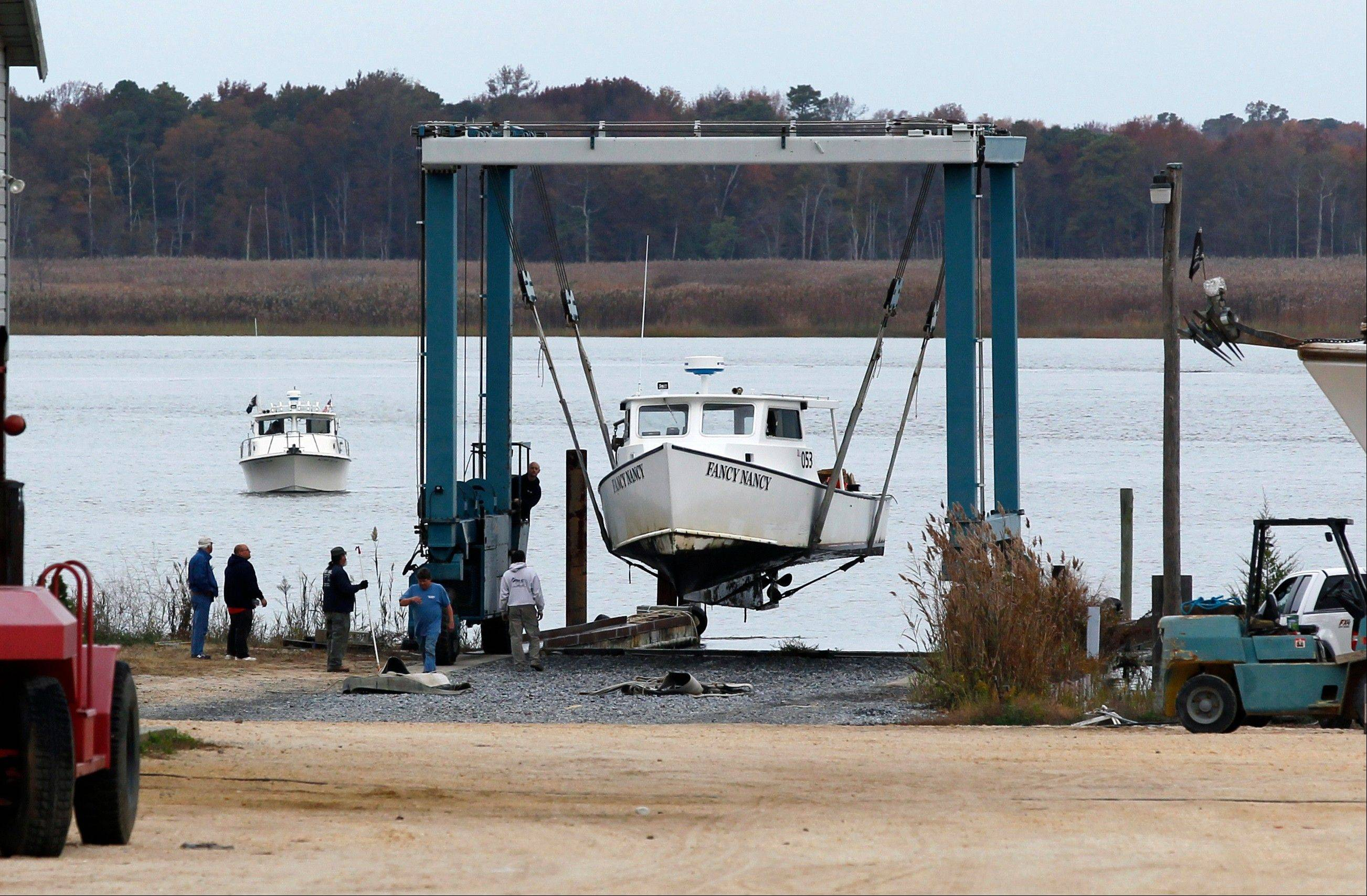 As another boat waits its turn, a 50-ton lift raises Fancy Nancy, a 40-foot commercial fishing boat, out of the Maurice River at Yank Marine Services marina Saturday, Oct. 27, 2012, in Dorchester, N.J., in preparation for Hurricane Sandy.