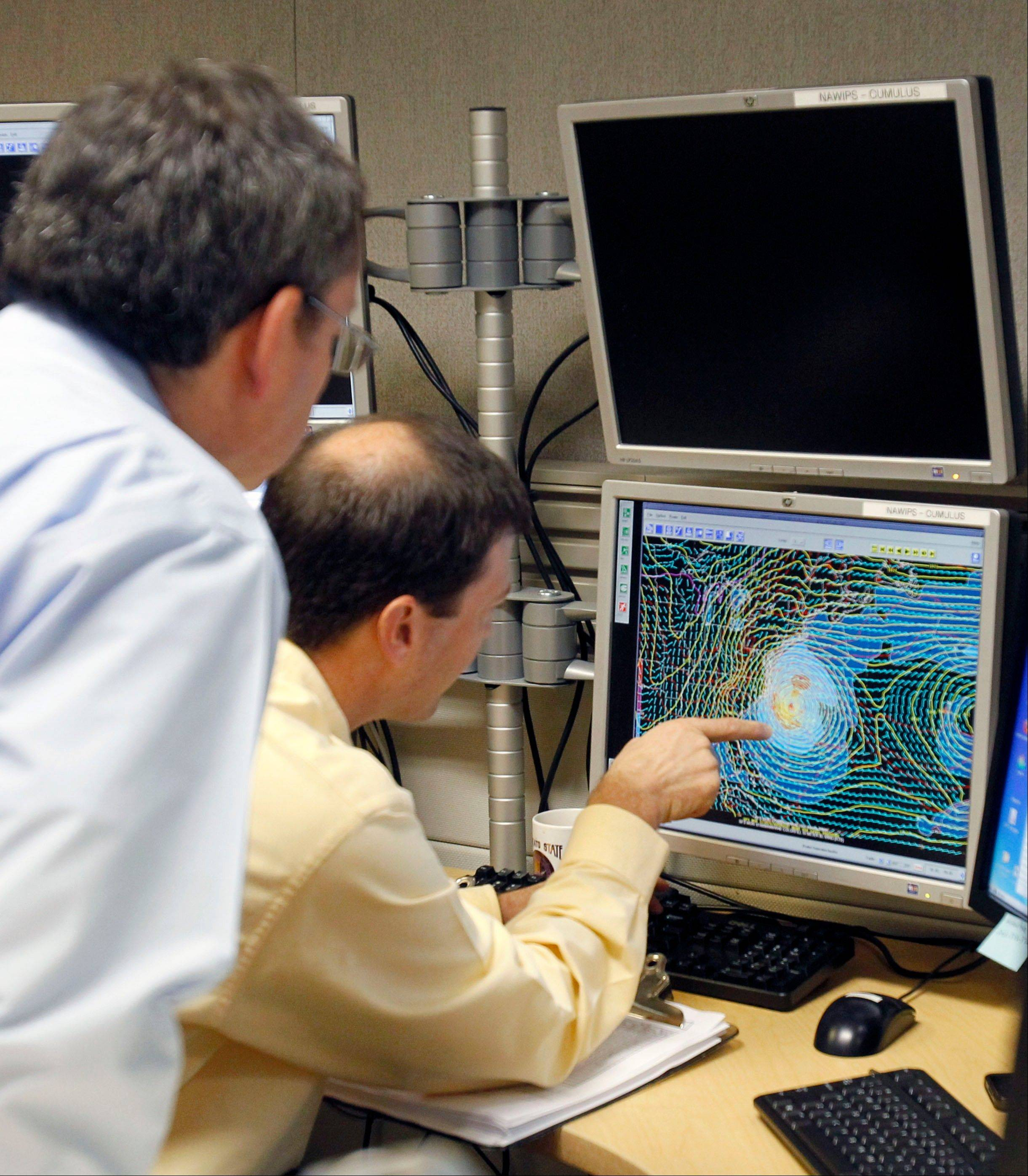 Senior hurricane specialist Dan Brown, right, points to a satellite image of Sandy to James Franklin, chief hurricane specialist, in preparation of the 11:00 EDT advisory at the National Hurricane Center in Miami, Saturday, Oct. 27, 2012. Early Saturday, the storm was about 335 miles southeast of Charleston, S.C.
