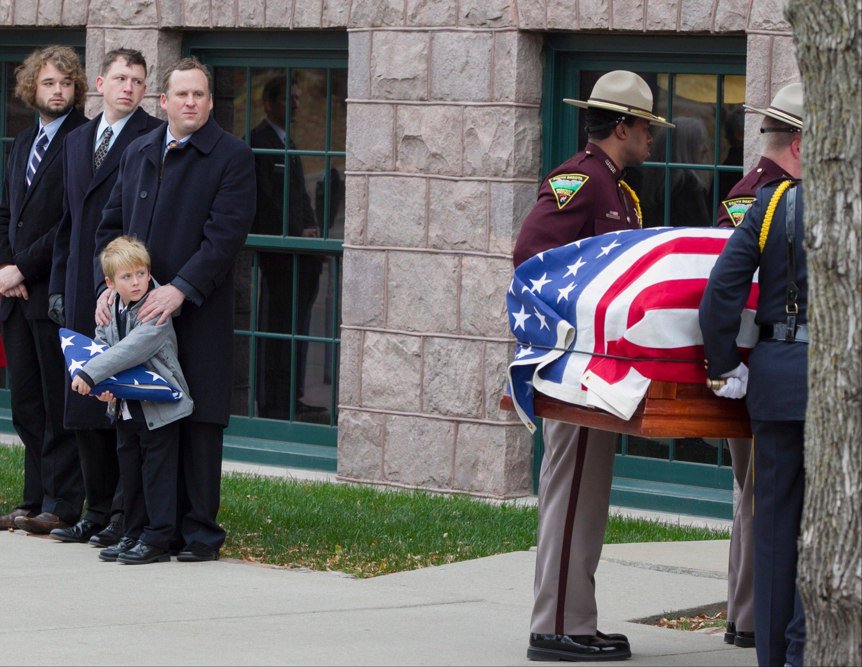 Will Mead holds a tri-folded flag as he watches Friday with family members the casket of his great grandfather, former Democratic U.S. Senator and three-time presidential candidate George McGovern, being carried into the Washington Pavilion of Arts and Science in Sioux Falls, S.D.