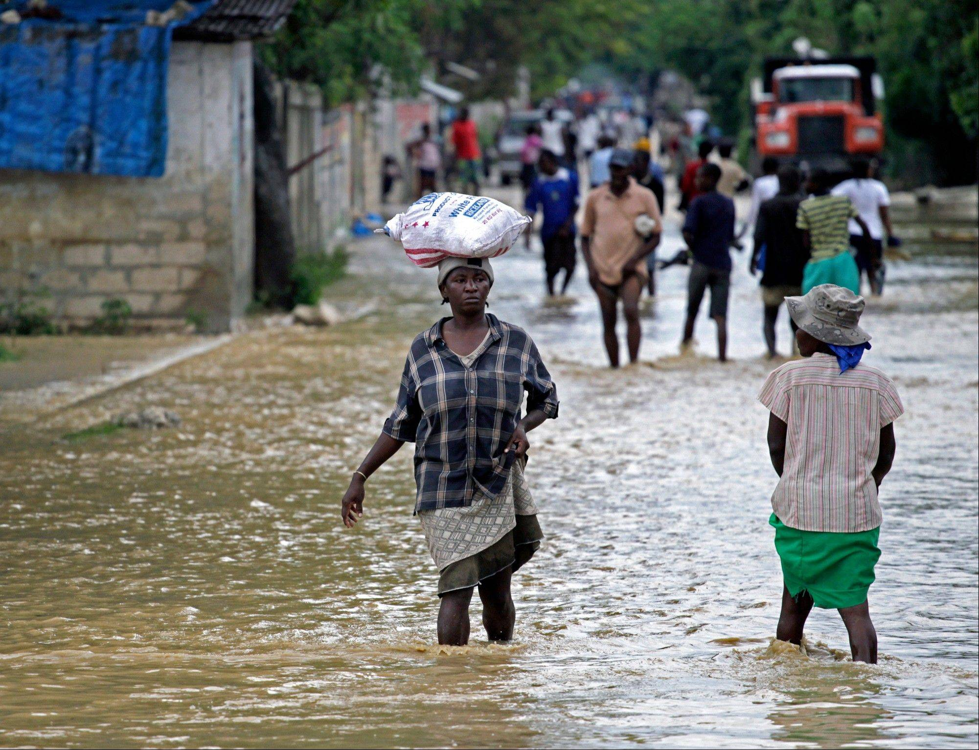 Associated Press Locals walk across the flooded streets of La Plaine, Haiti, Thursday.