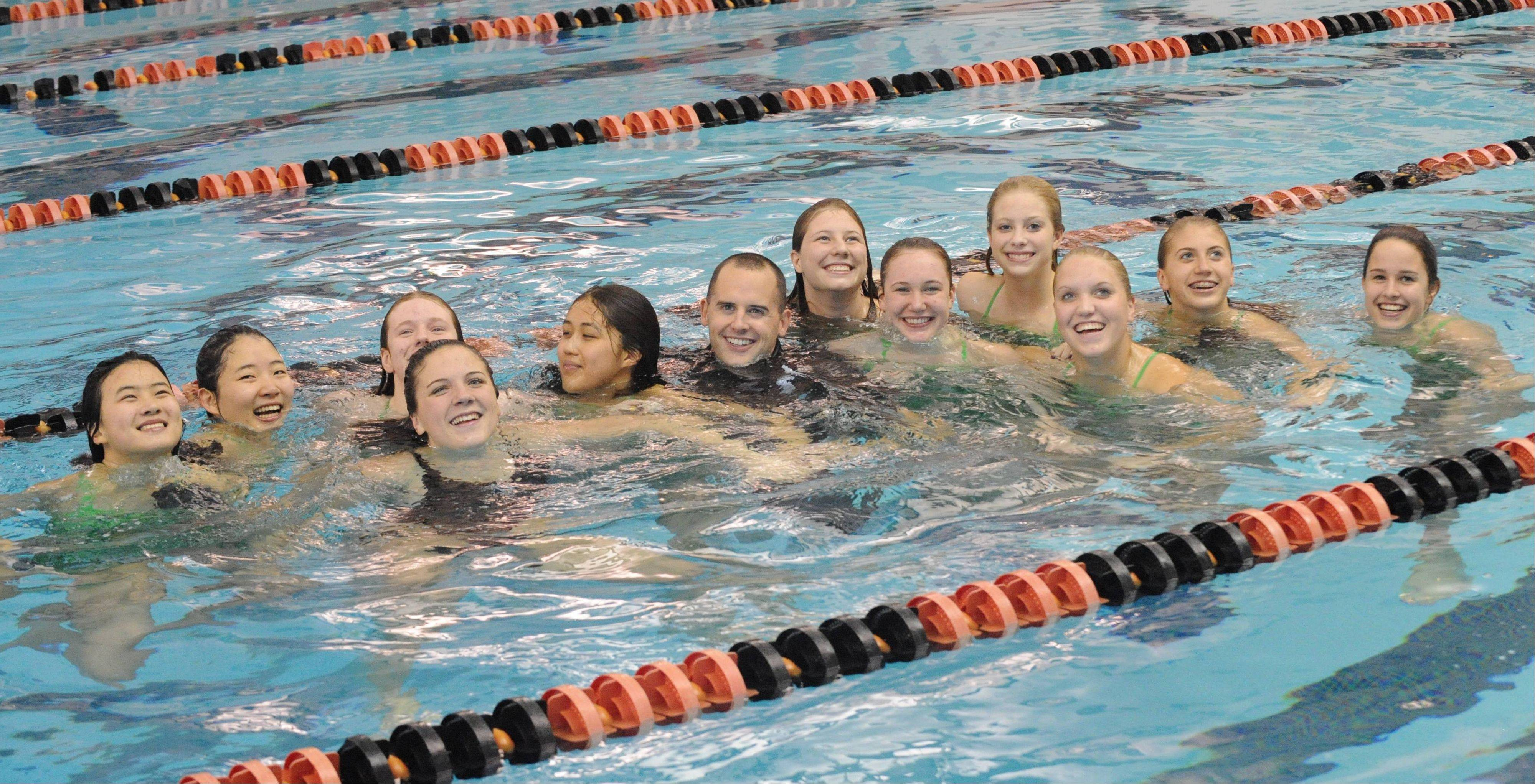 Coach Andrew Kittrell, middle, soaks up a winning team effort with his Fremd swimmers after Saturday's Mid-Suburban League meet at Barrington.