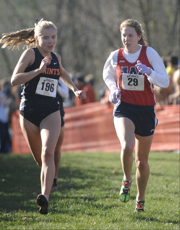 St. Charles East's Sarah Hill and West Aurora's Claire Loran fight to the finish line in the cross country sectional at LeRoy Oakes in St. Charles on Saturday, October 27.