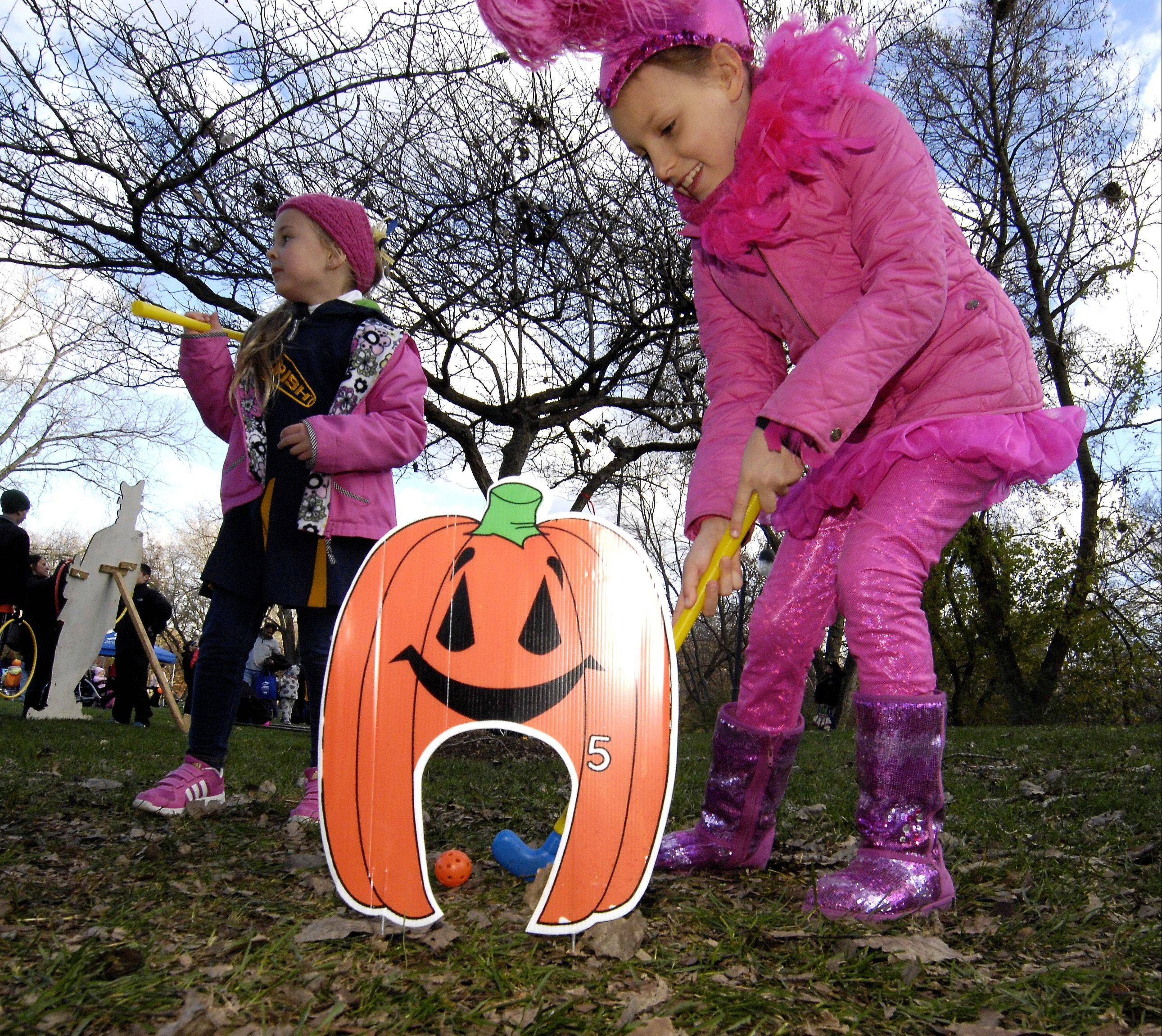 Victoria Blasko, 8, putts through a jack-o�-lantern while Sofia Bargen, 6, waits her turn during the Naperville Park District�s Halloween Happening Sunday at the Grand Pavilion. Other events in downtown Naperville included trick-or-treating and the Naperville Park District�s Halloween Happening at the Grand Pavilion.