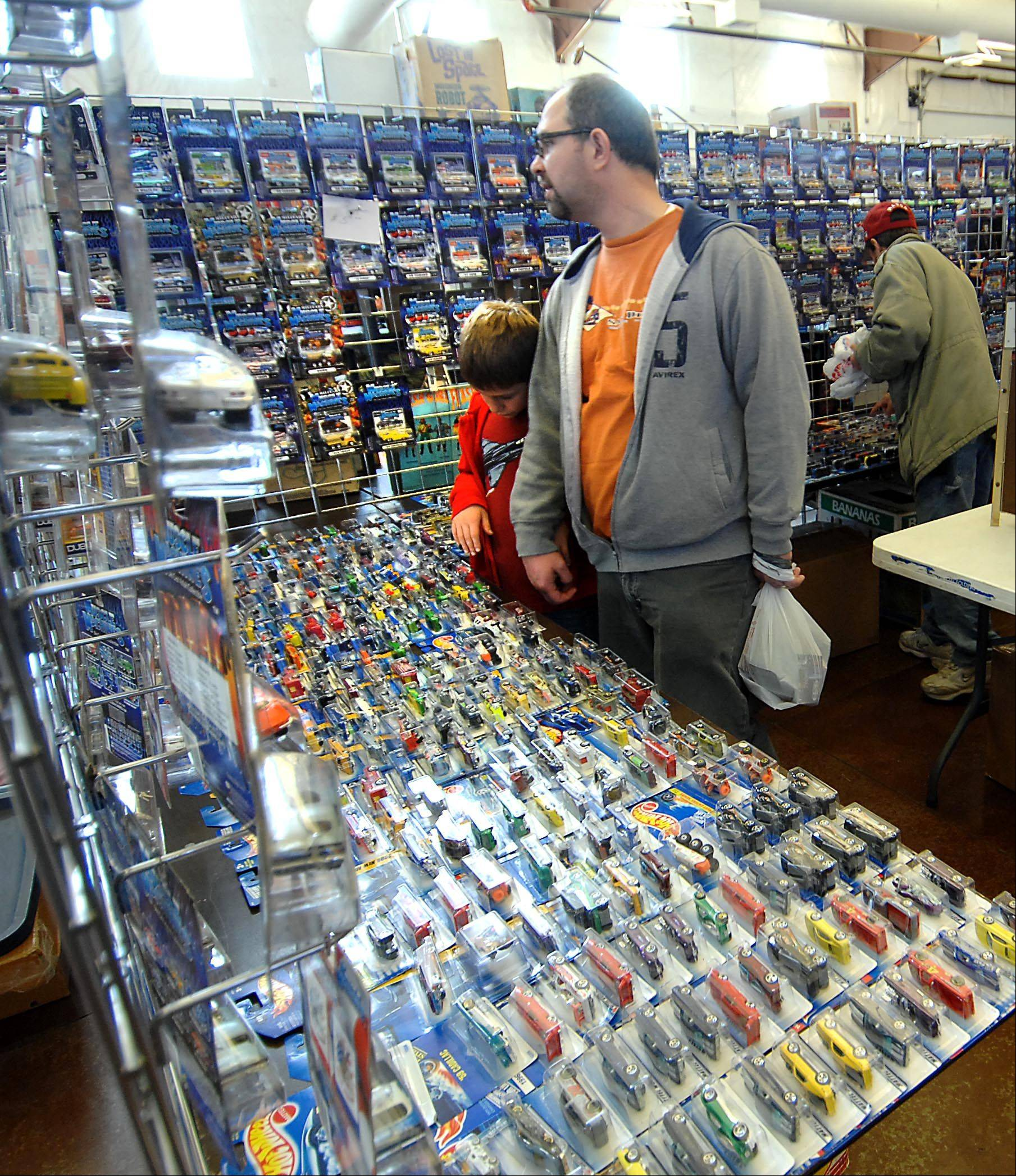 Noah Ivicic, 10, and his dad Chris, of Mokena, look over a table of Hot Wheels Sunday at the Chicago Toy Show at the Kane County Fairgrounds in St. Charles. Four buildings were filled with collectible toys for sale.