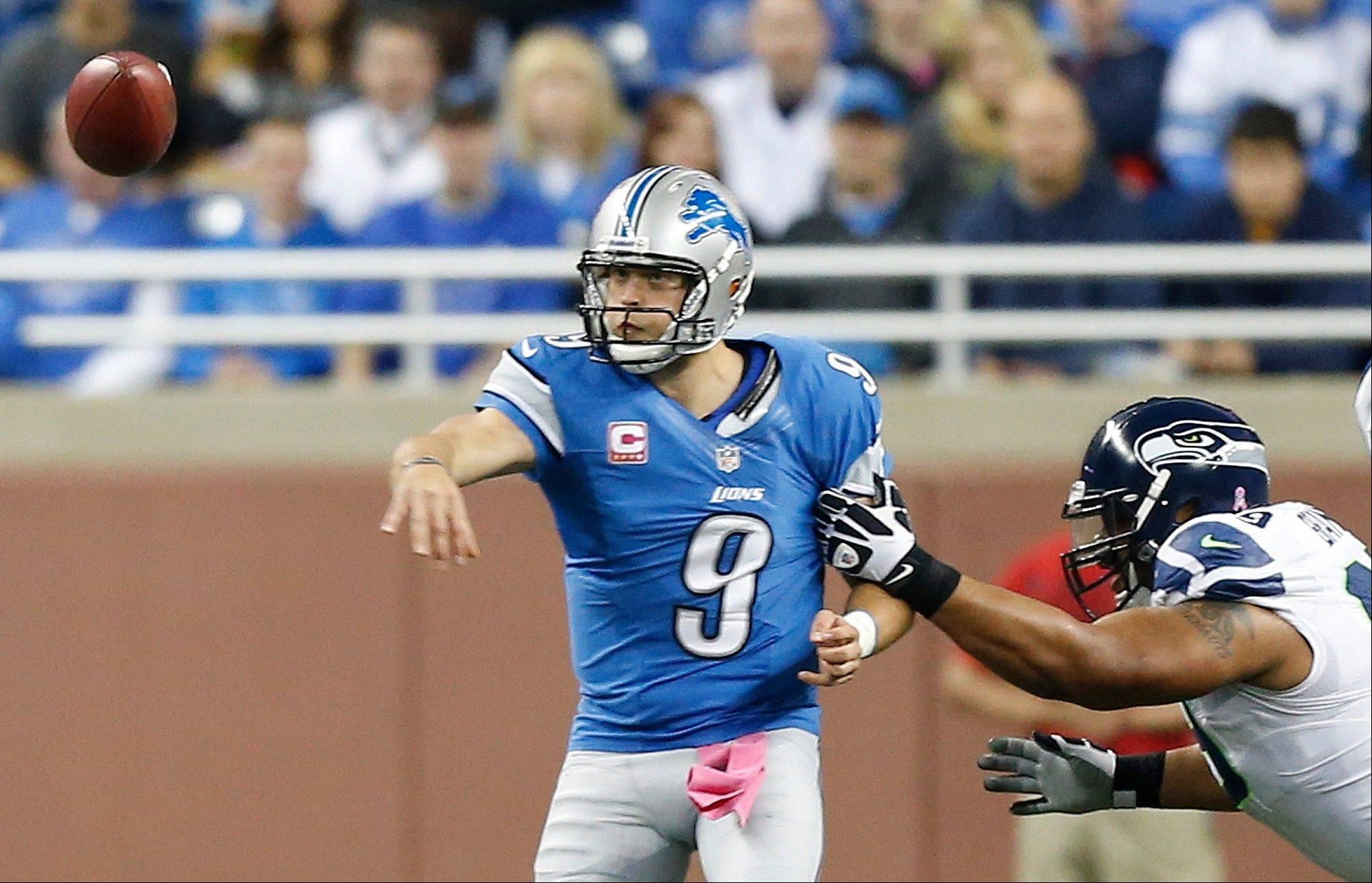 Detroit Lions quarterback Matthew Stafford (9) throws a pass as Seattle Seahawks defensive tackle Alan Branch (99) puts pressure on the quarterback in the first half in Detroit.