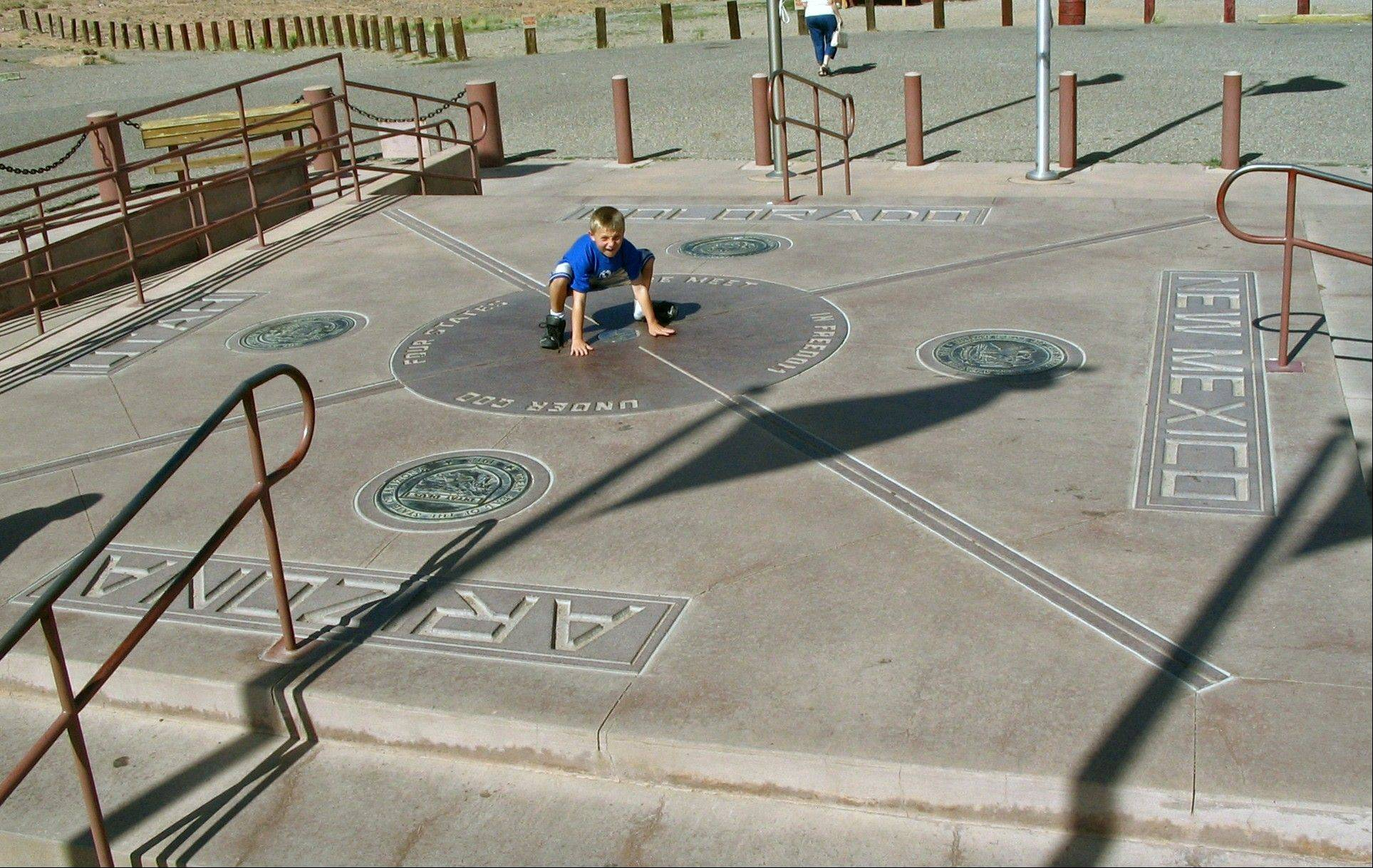 "A boy touched four border states -- New Mexico, Arizona, Utah and Colorado -- at Four Corners National Monument. Visiting all 50 states is a popular goal among some travelers, though criteria vary as to what ""counts"" for crossing a place off your list."