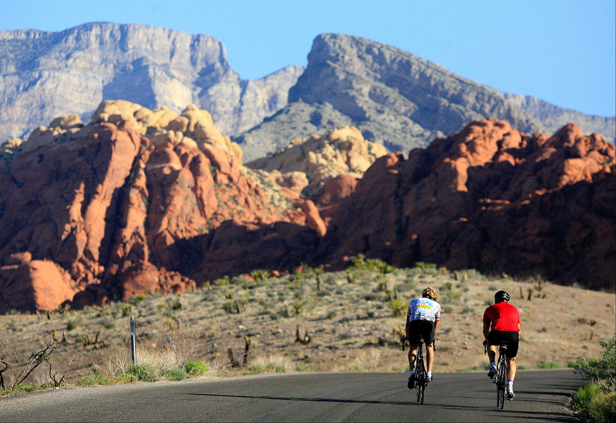Two cyclists ride along the 13-mile-long scenic drive at Red Rock Canyon National Conservation Area in Nevada. These towering red sandstone cliffs, some reaching 3,000 feet, are just 15 miles west of metropolitan Las Vegas.