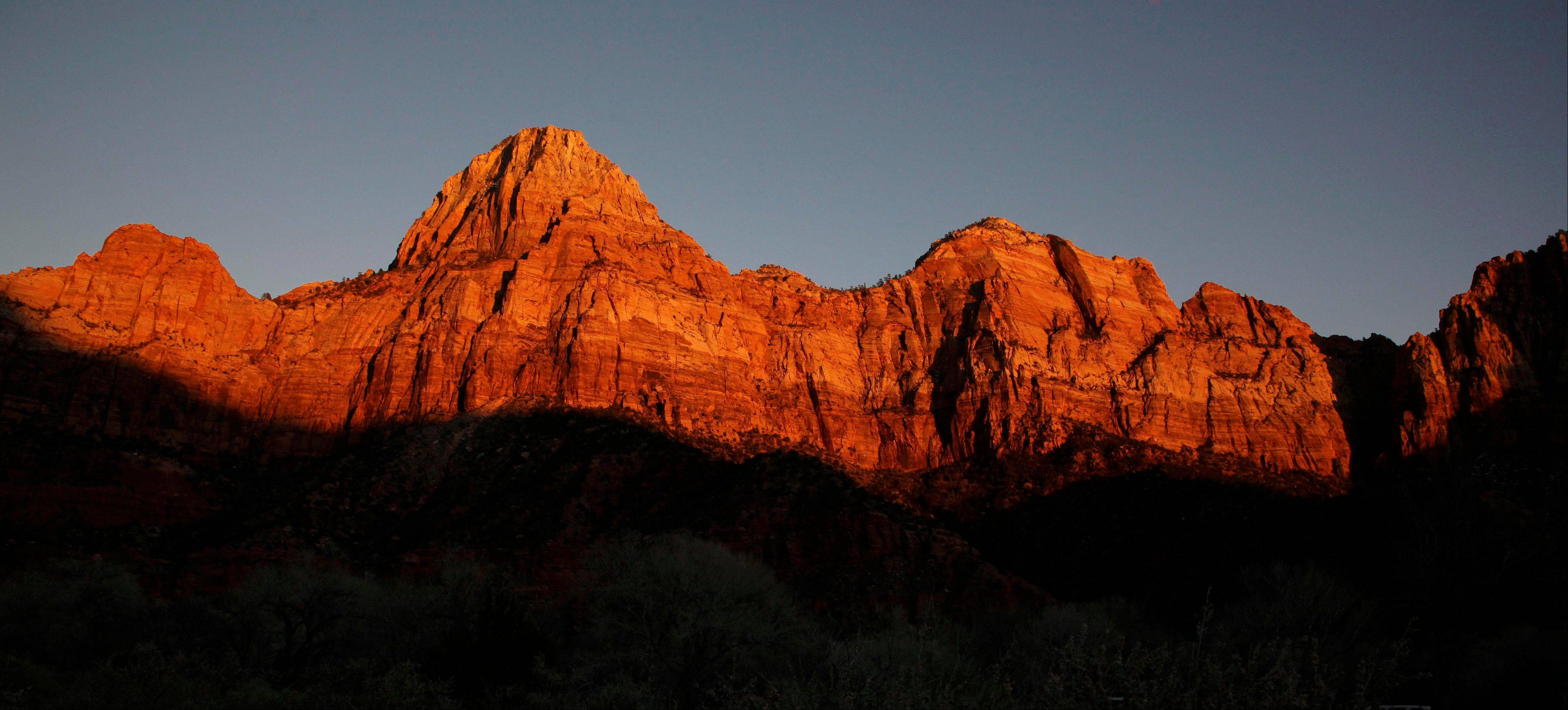 Shadows creep up on sandstone cliffs glowing red as the sun sets on Zion National Park near Springdale, Utah.