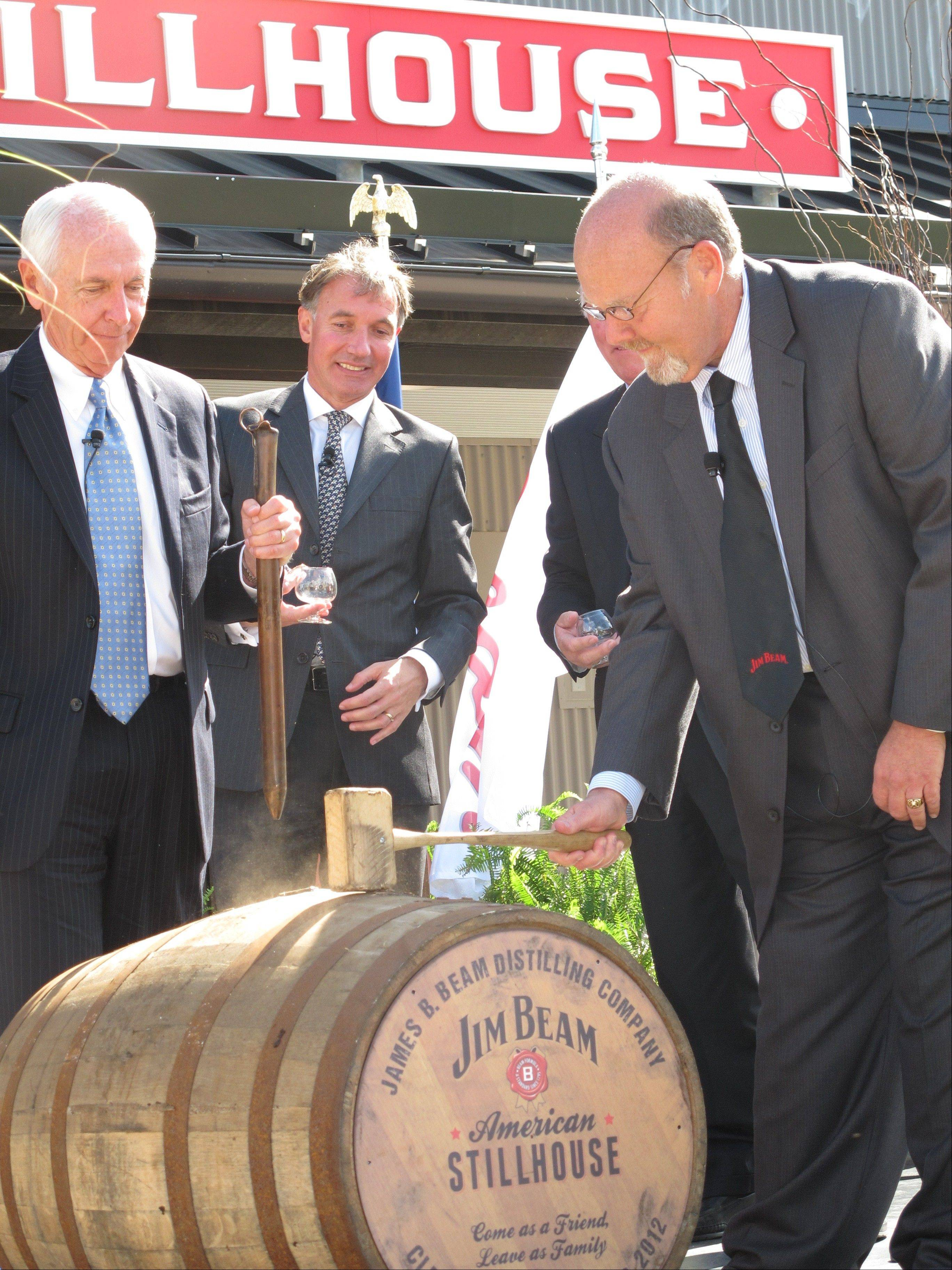 Jim Beam master distiller Fred Noe, right, opening a barrel of whiskey at Clermont, Ky., to celebrate the opening of a new visitors center at the distillery. The $20 million center is part of a wave of new or expanded visitors centers at Kentucky bourbon distilleries to cater to growing numbers of tourists.