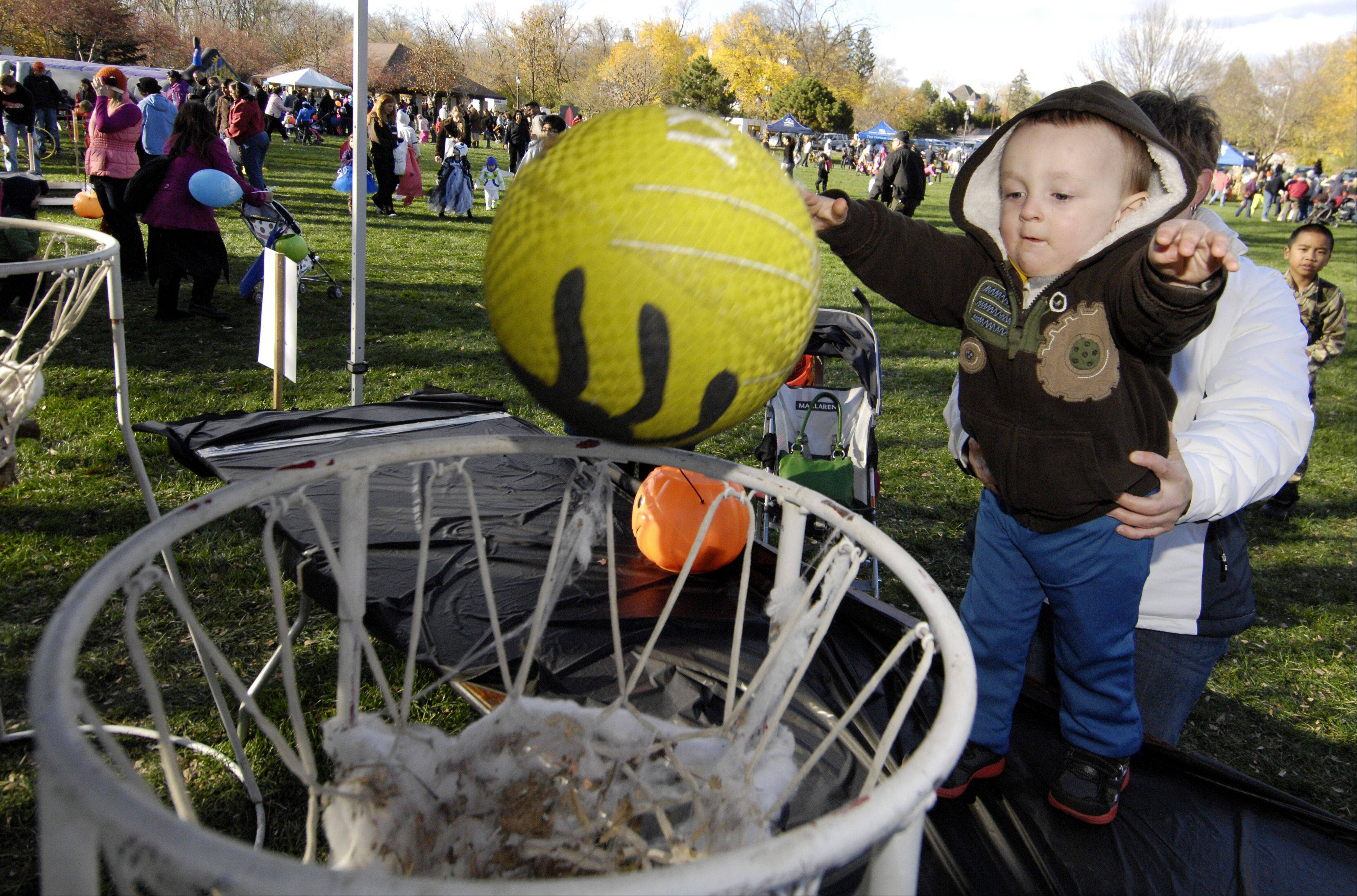 "Stanley Waite, 2, of Oak Brook, takes a basketball shot into a ""spooky spider web"" during the Naperville Park District's Halloween Happening Sunday at the Grand Pavilion."