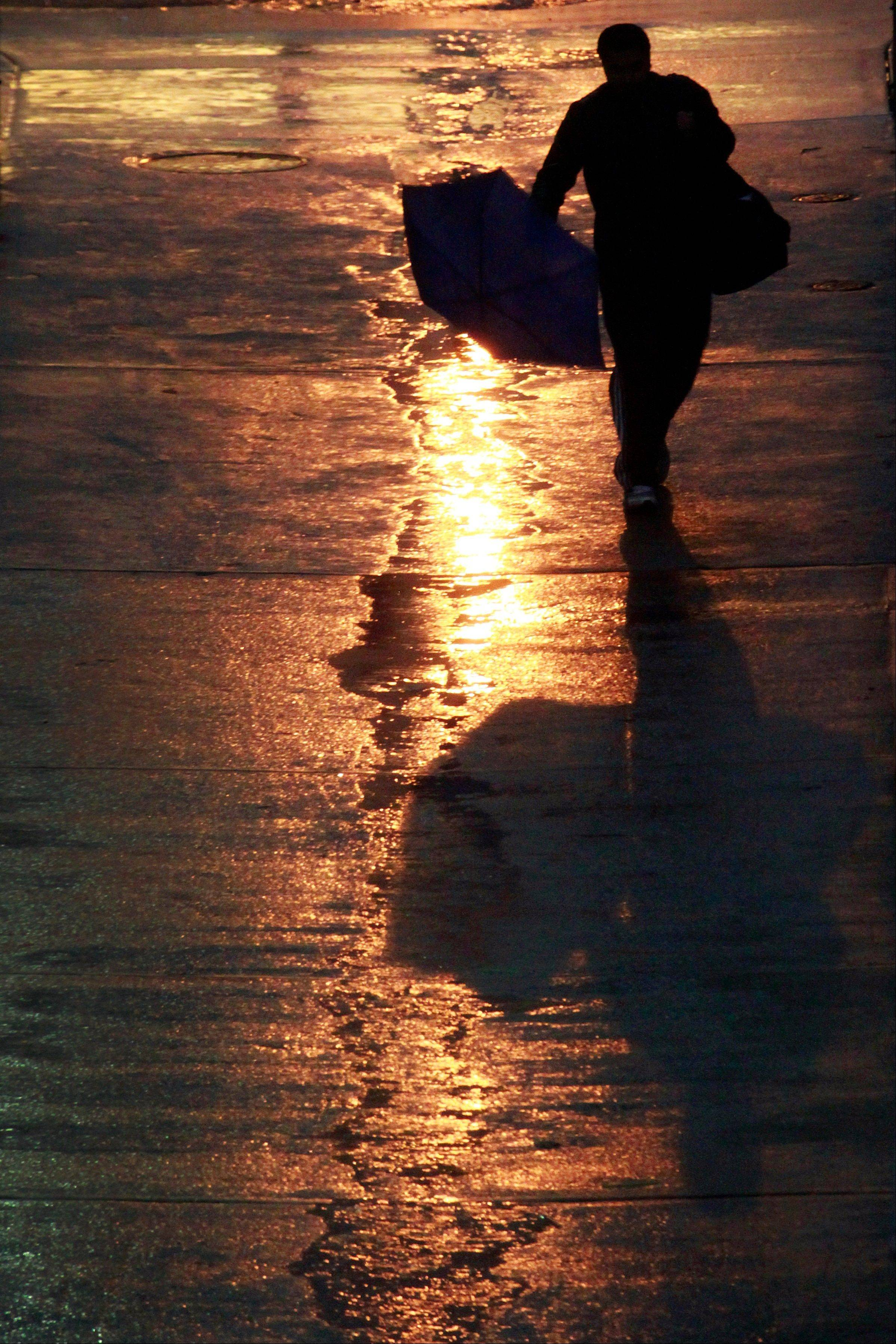 A pedestrian walks through light rain early Monday morning in Washington as Hurricane Sandy approaches the east coast. The wind and rain in the Nation's Capitol is expected to increase though out the day.