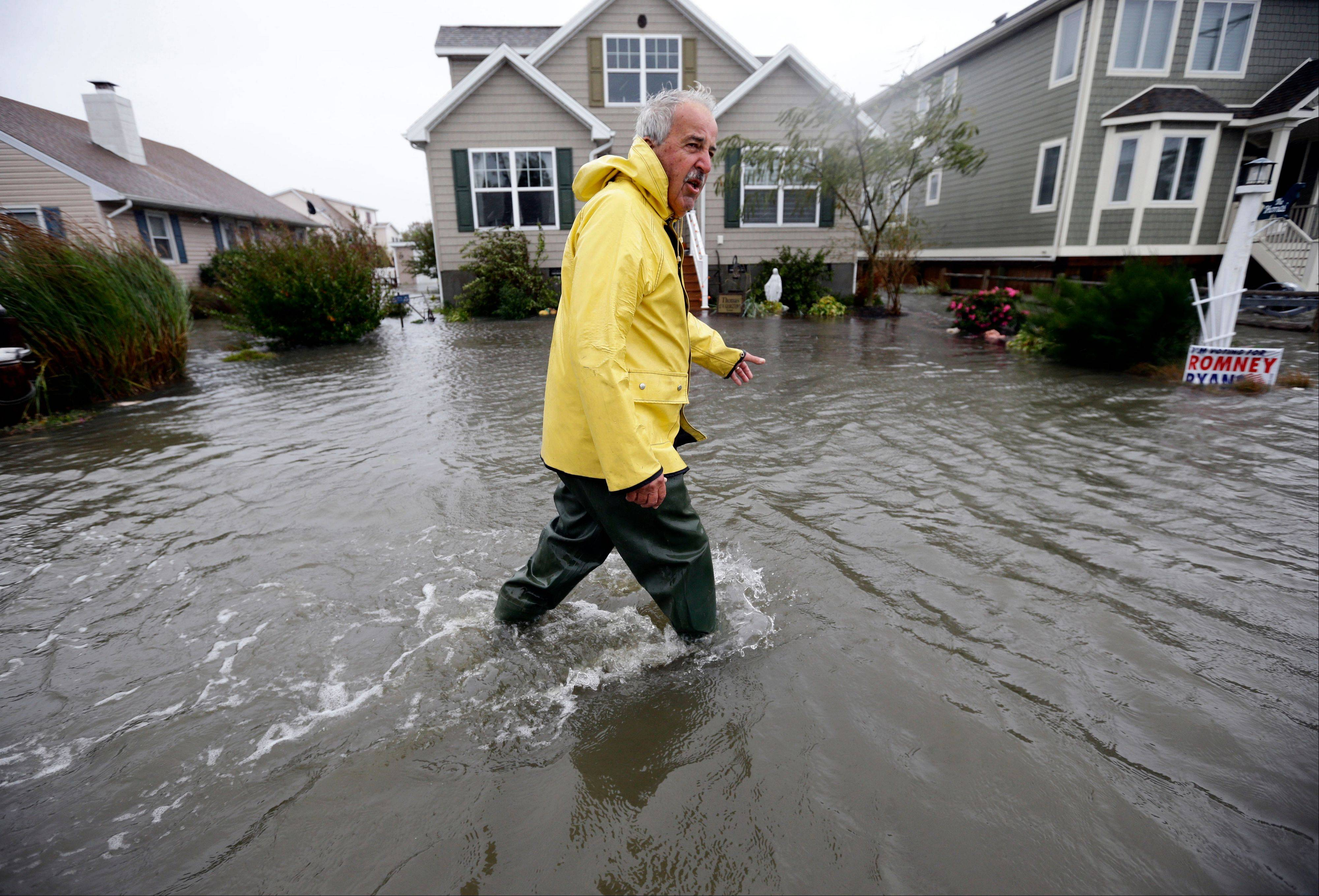 Richard Thomas walks through the floodwaters in front of his home after assisting neighbors as Hurricane Sandy bears down on the East Coast, Monday in Fenwick Island, Del.